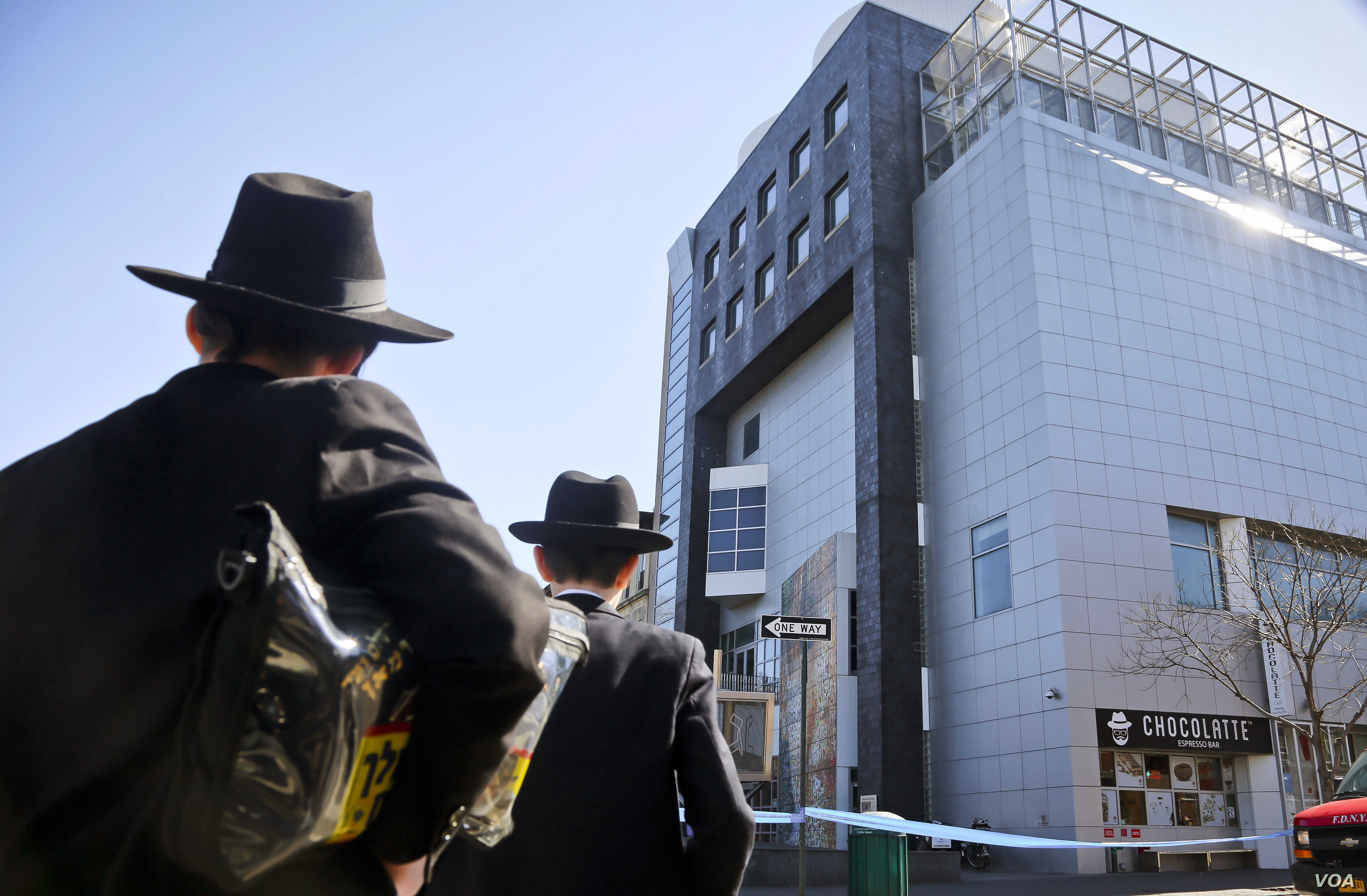 FILE - Two young men who left a nearby synagogue watch police activity outside the Jewish Children's Museum following a bomb threat in Brooklyn borough of New York, March 9, 2017. Authorities say an Israeli Jewish teen is responsible for the threats...