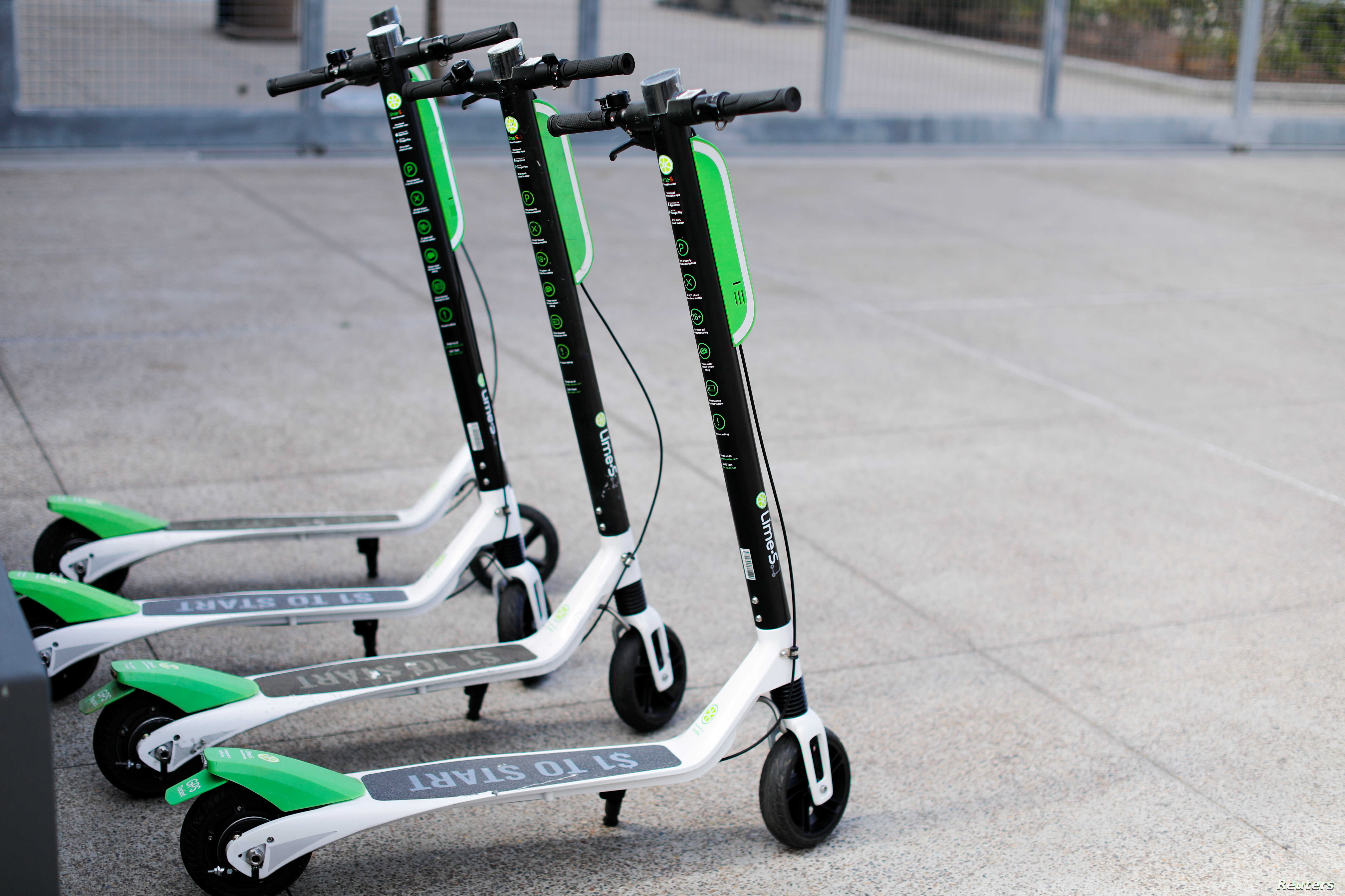 Smart phone app time-of-use electric scooters from Lime-S are shown parked along a sidewalk in San Diego, California, May 17, 2018.