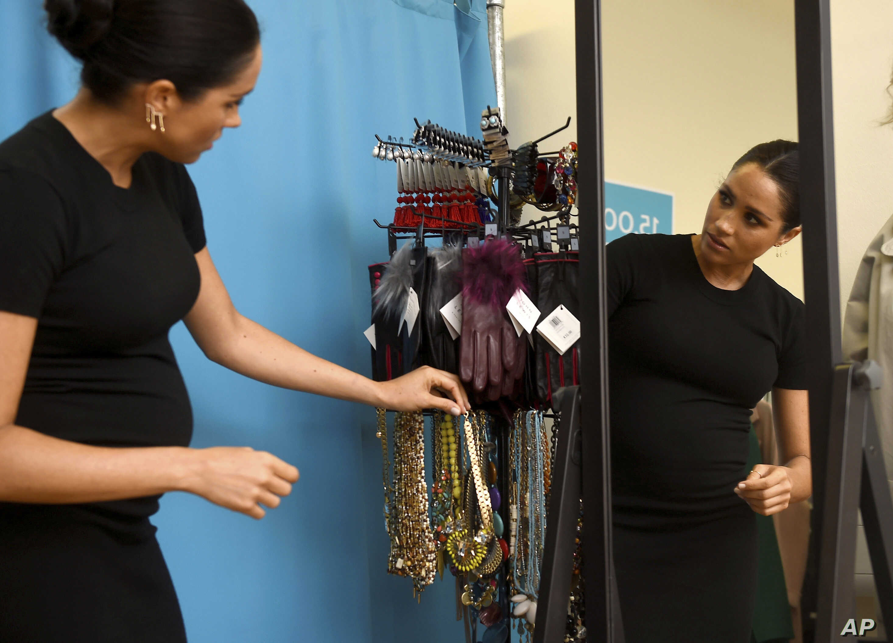 Meghan, the Duchess of Sussex, who is expecting her first child in spring, is reflected in a mirror at right, as she inspects clothes intended for women returning to work during a visit to Smart Works career centre in West London, Jan. 10, 2019.