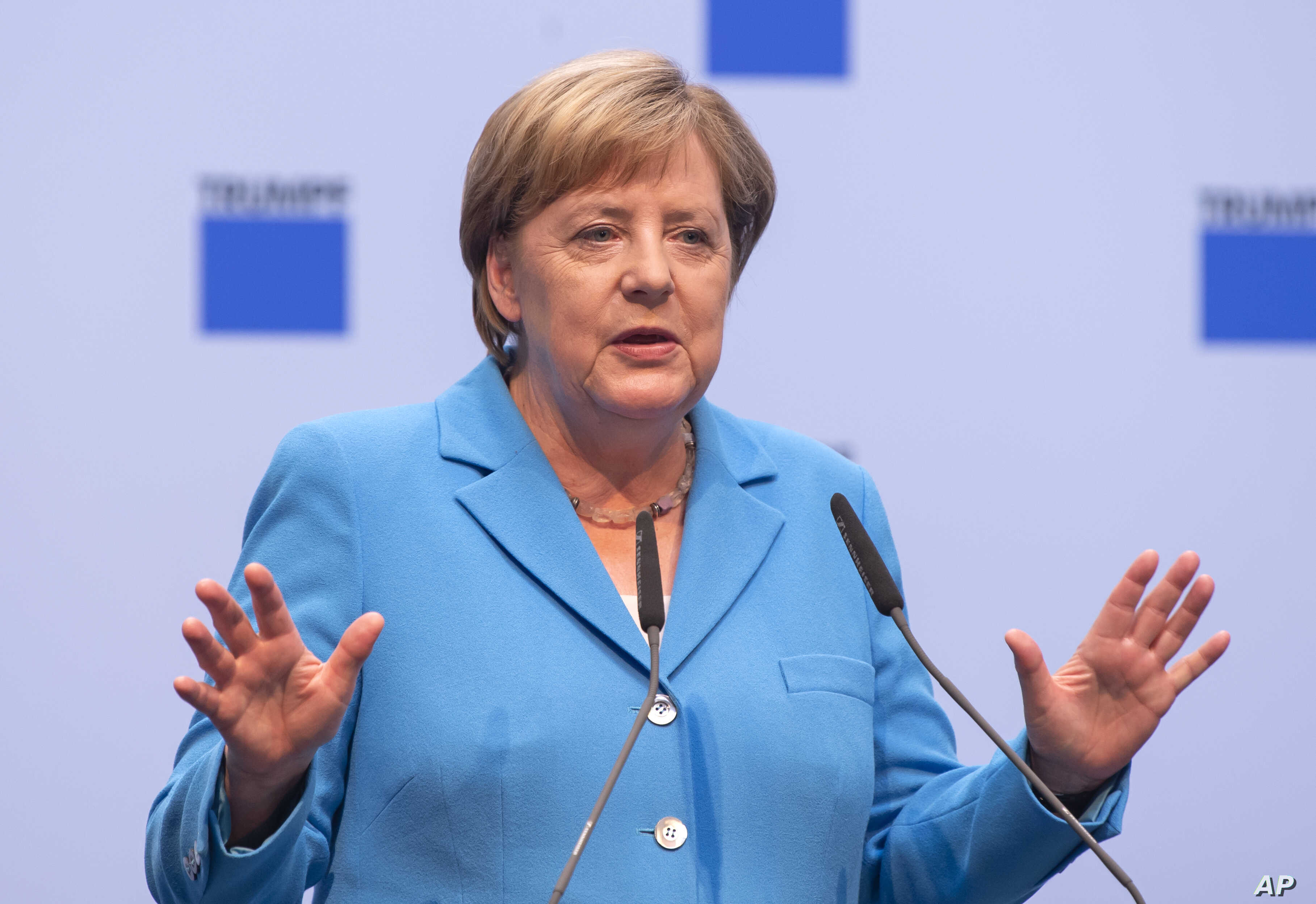 German chancellor Angela Merkel gestures during a discussion with TRUMPF employees in Neukirch, eastern Germany,  Aug. 16, 2018.