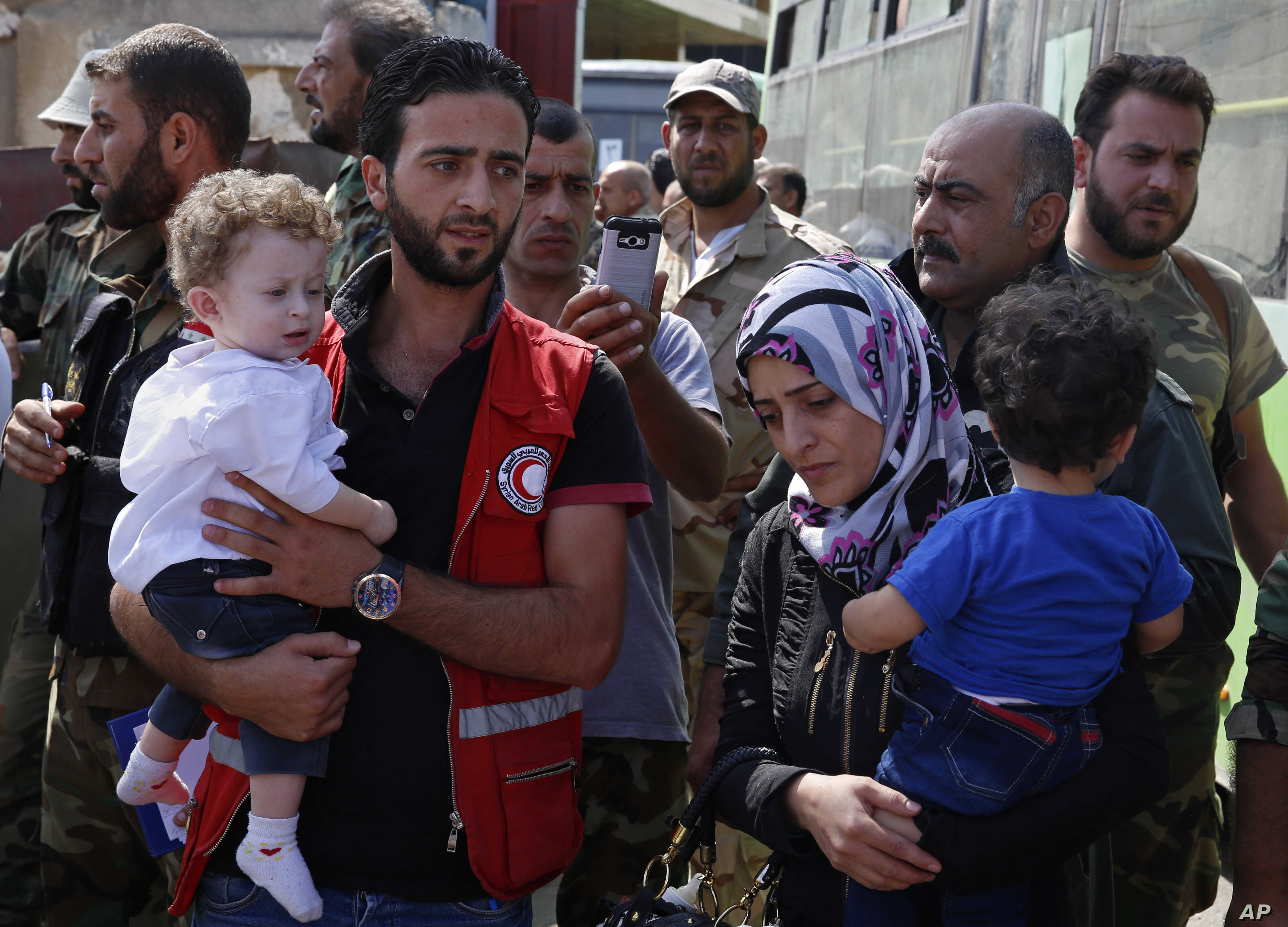 Staffers of the Syrian Arab Red Crescent assist families of gunmen as they leave from Al-Waer, the last rebel-held neighborhood of Homs, Syria, Sept. 22, 2016.