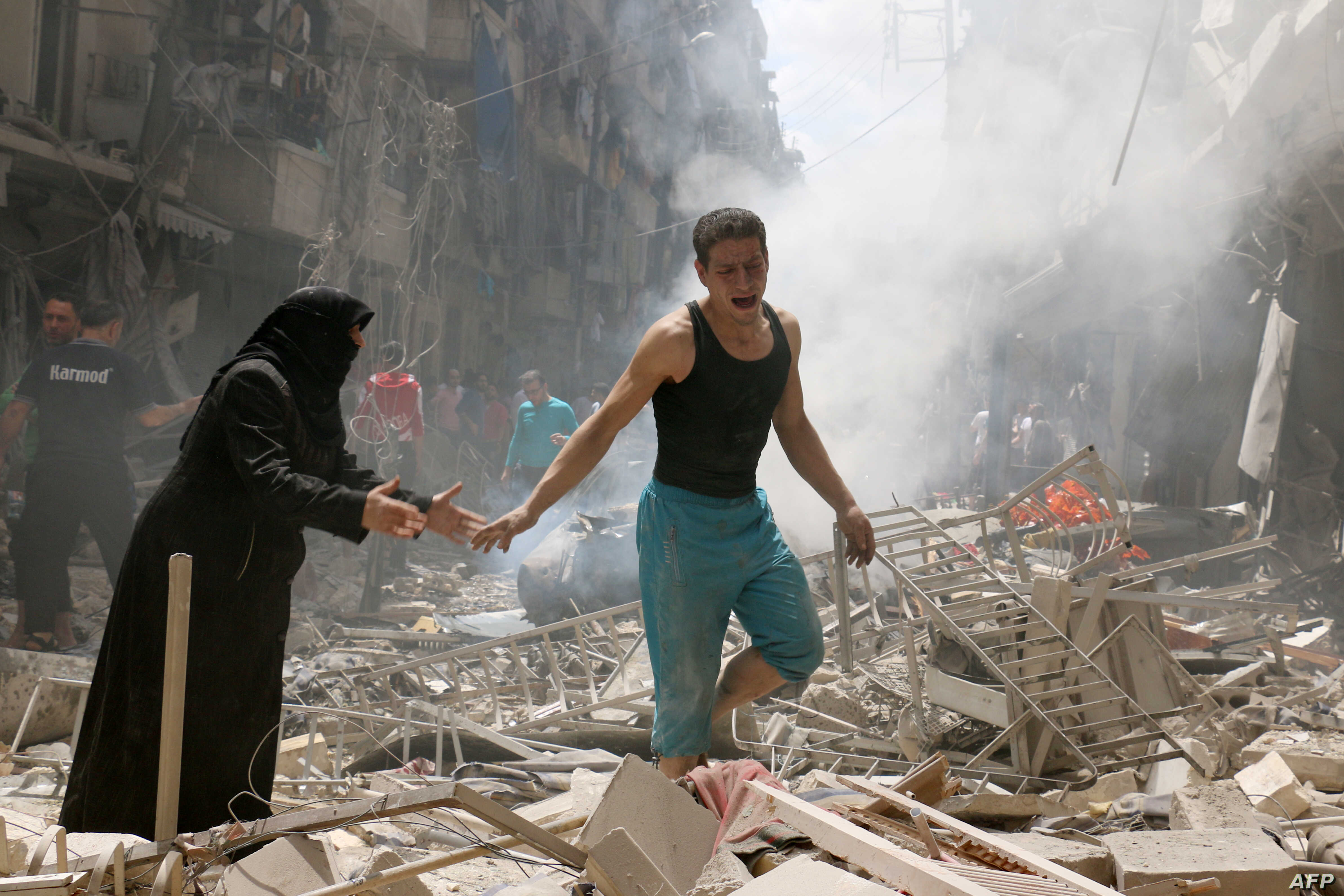People walk amid the rubble of destroyed buildings following a reported air strike on the rebel-held neighborhood of al-Kalasa in the northern Syrian city of Aleppo, on April 28, 2016.
