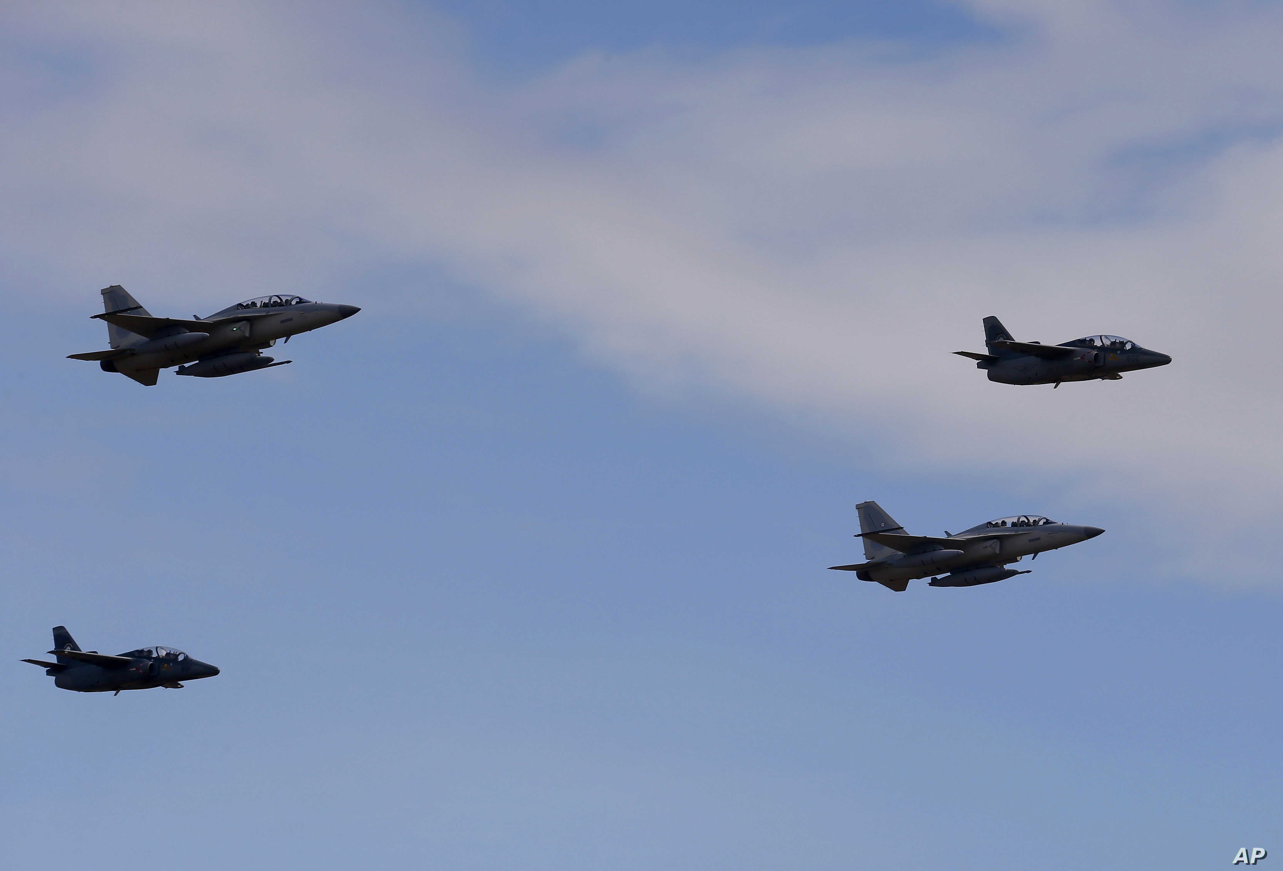 Newly-acquired FA-50PH fighter jets, top left and bottom right, escorted by Philippine Air Force S-211 jets, fly upon arrival in Philippine air space from South Korea, Nov. 28, 2015.