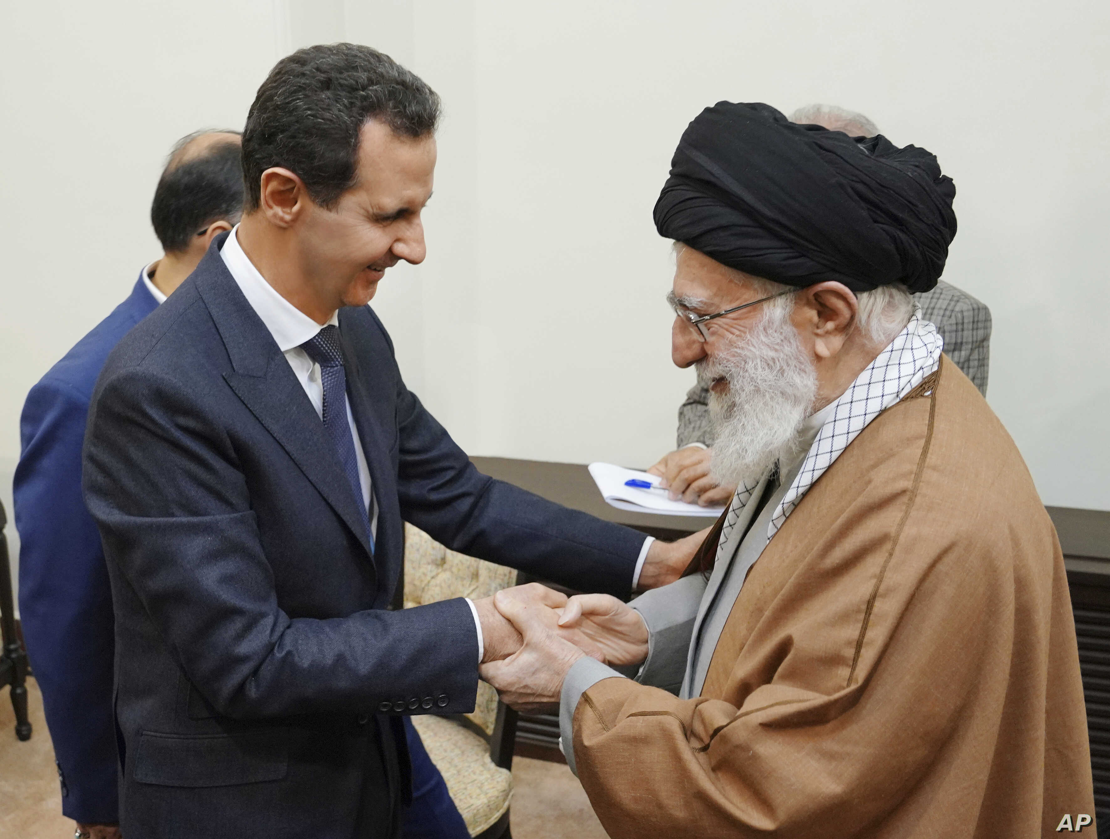 In this photo released by the Syrian official news agency SANA, Syrian President Bashar al-Assad, left, shakes hands with Iranian Supreme Leader Ayatollah Ali Khamenei, before their meeting in Tehran, Syria, Feb. 25, 2019.