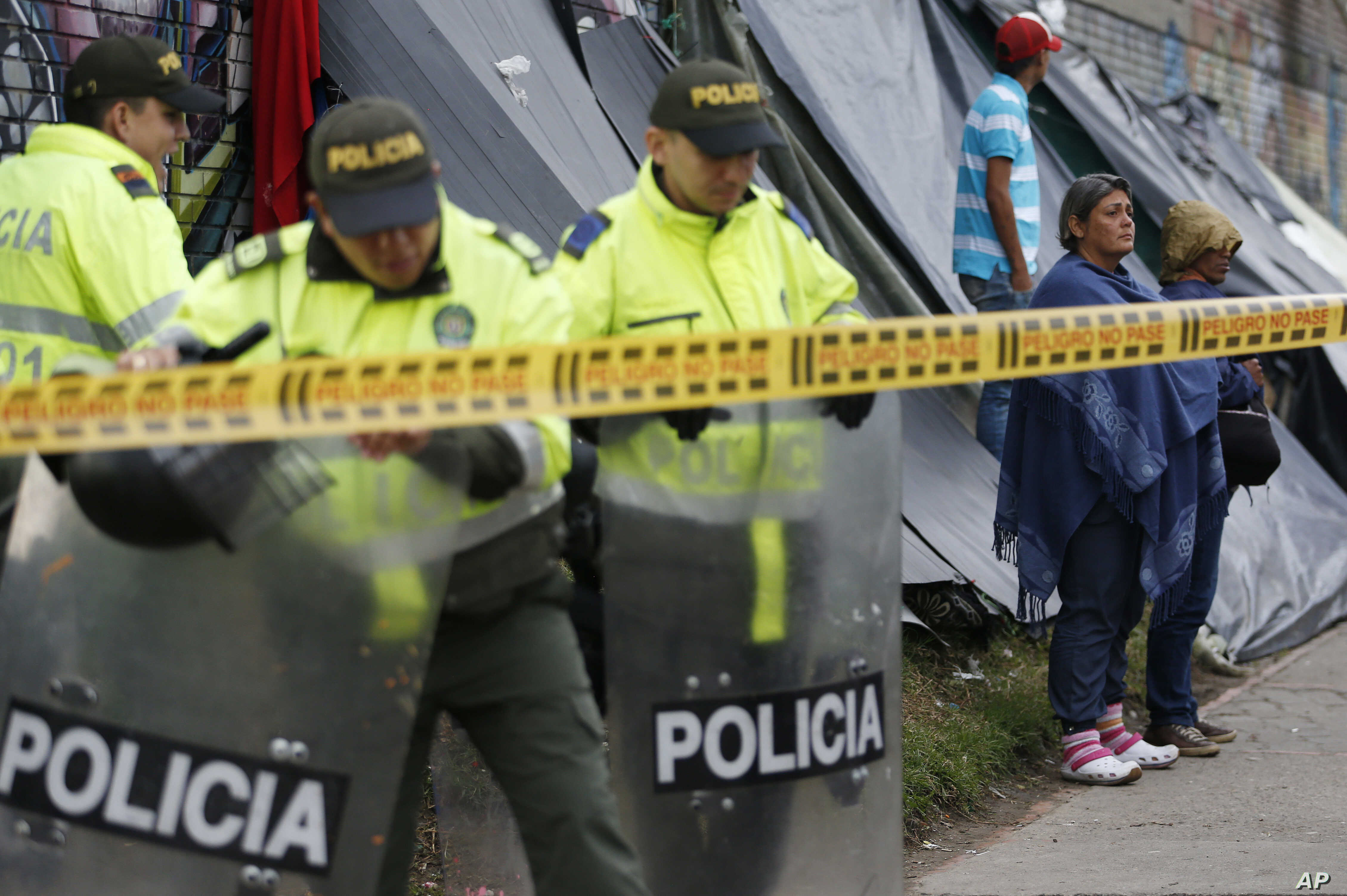 Police stand guard at a makeshift migrant settlement near the main bus terminal in Bogota, Colombia, Nov. 13, 2018.