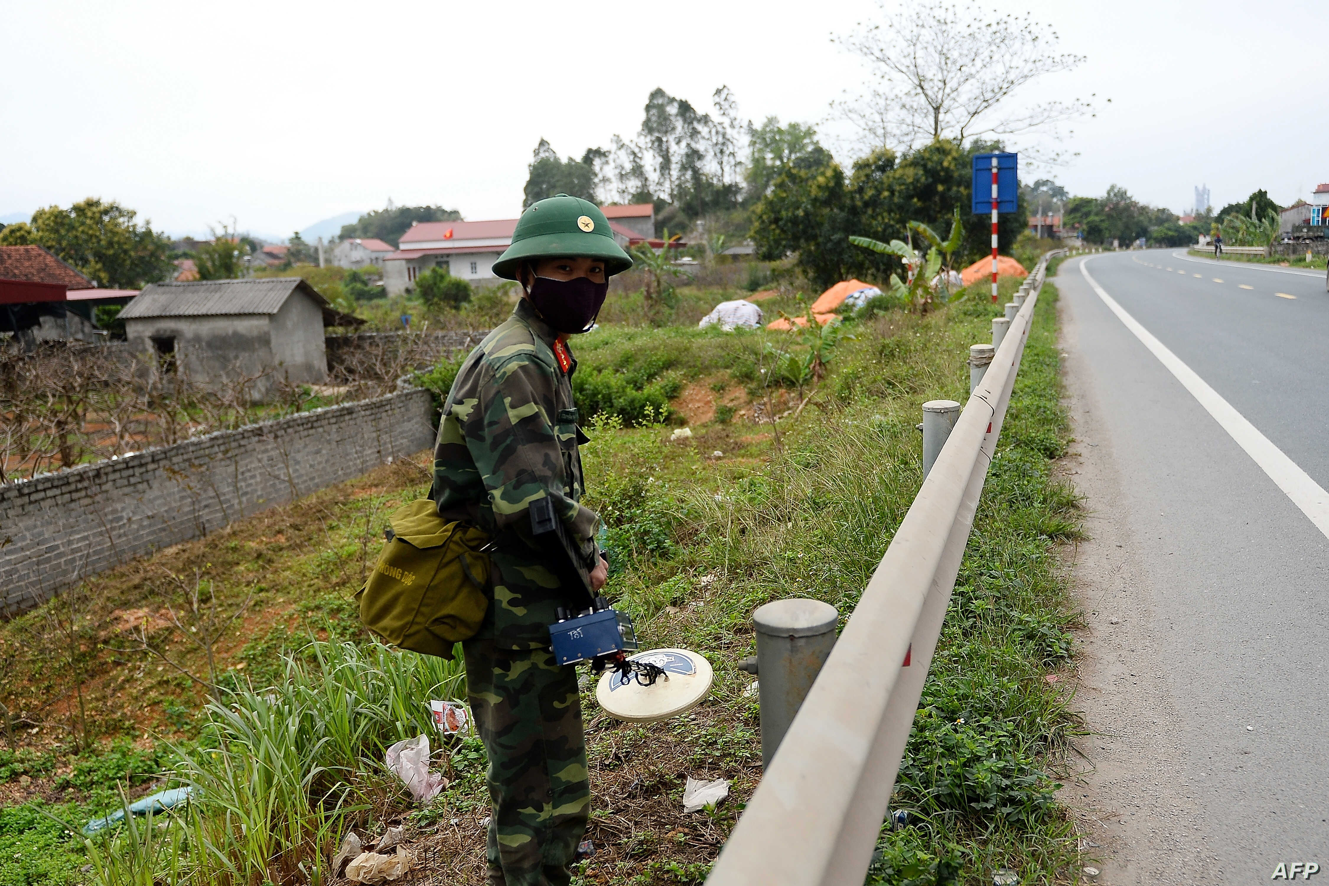 Vietnamese military personnel uses a mine-sweeper while patrolling the road between Hanoi and the Dong Dang railway station near the Chinese border in Lang Son province, Feb. 23, 2019.