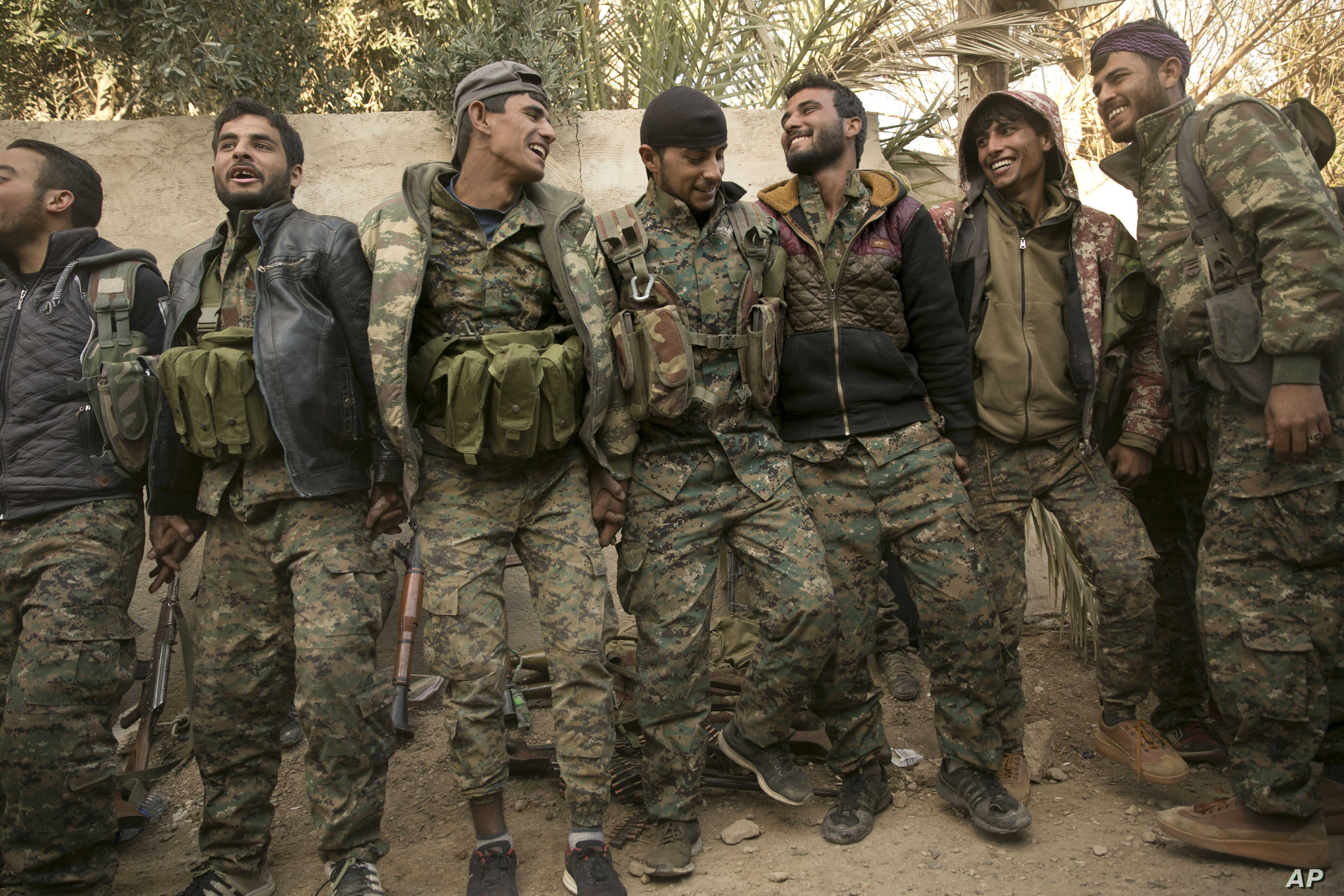 U.S.-backed Syrian Democratic Forces fighters celebrate their territorial gains over Islamic State militants in Baghuz, Syria, March 19, 2019.