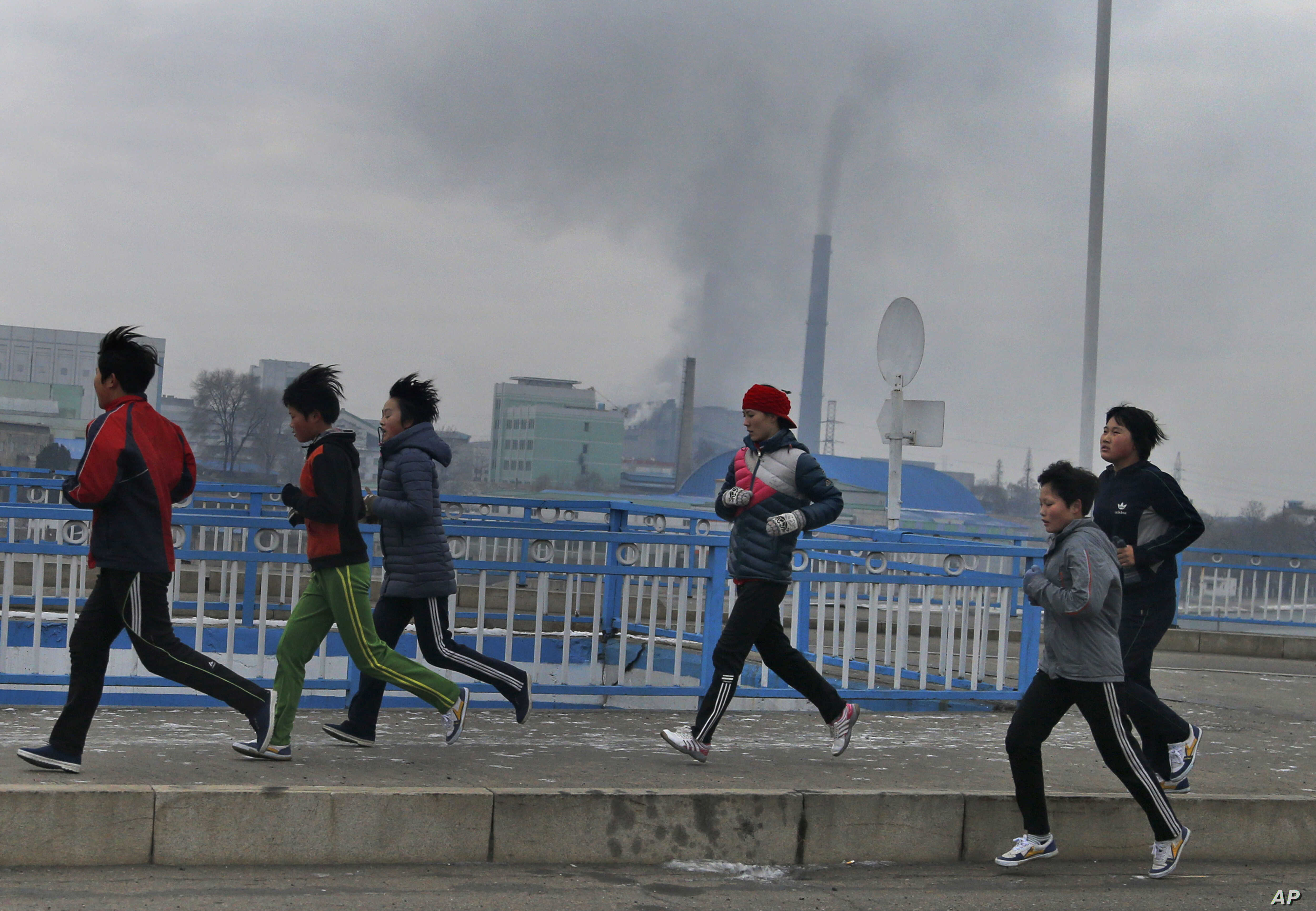 FILE - Young joggers pass by as smoke billows from the stack of the Pyongyang Power Plant in Pyongyang, North Korea, Dec. 15, 2018.