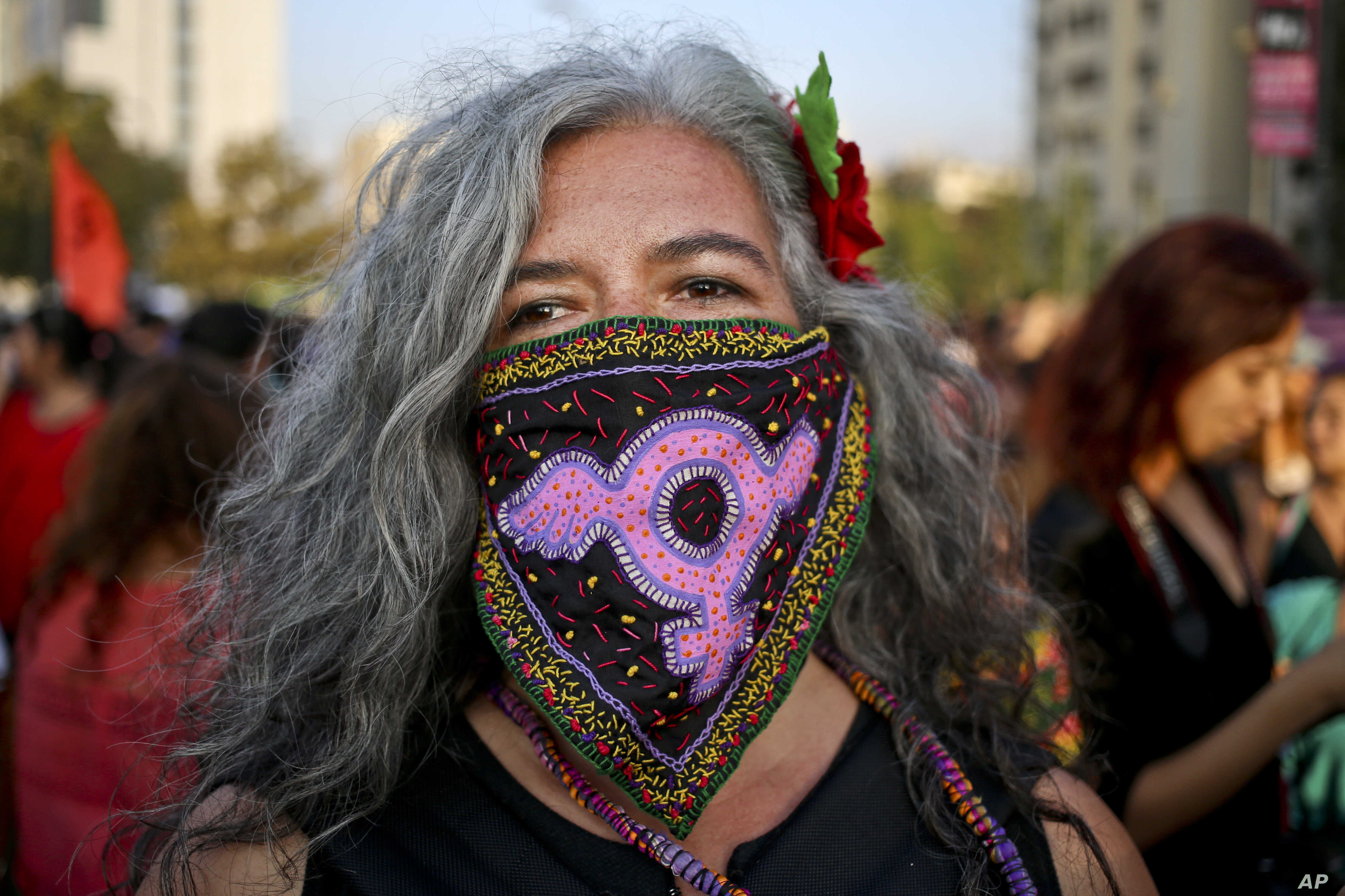 FILE - A woman takes part in an International Women's Day march in Santiago, Chile.