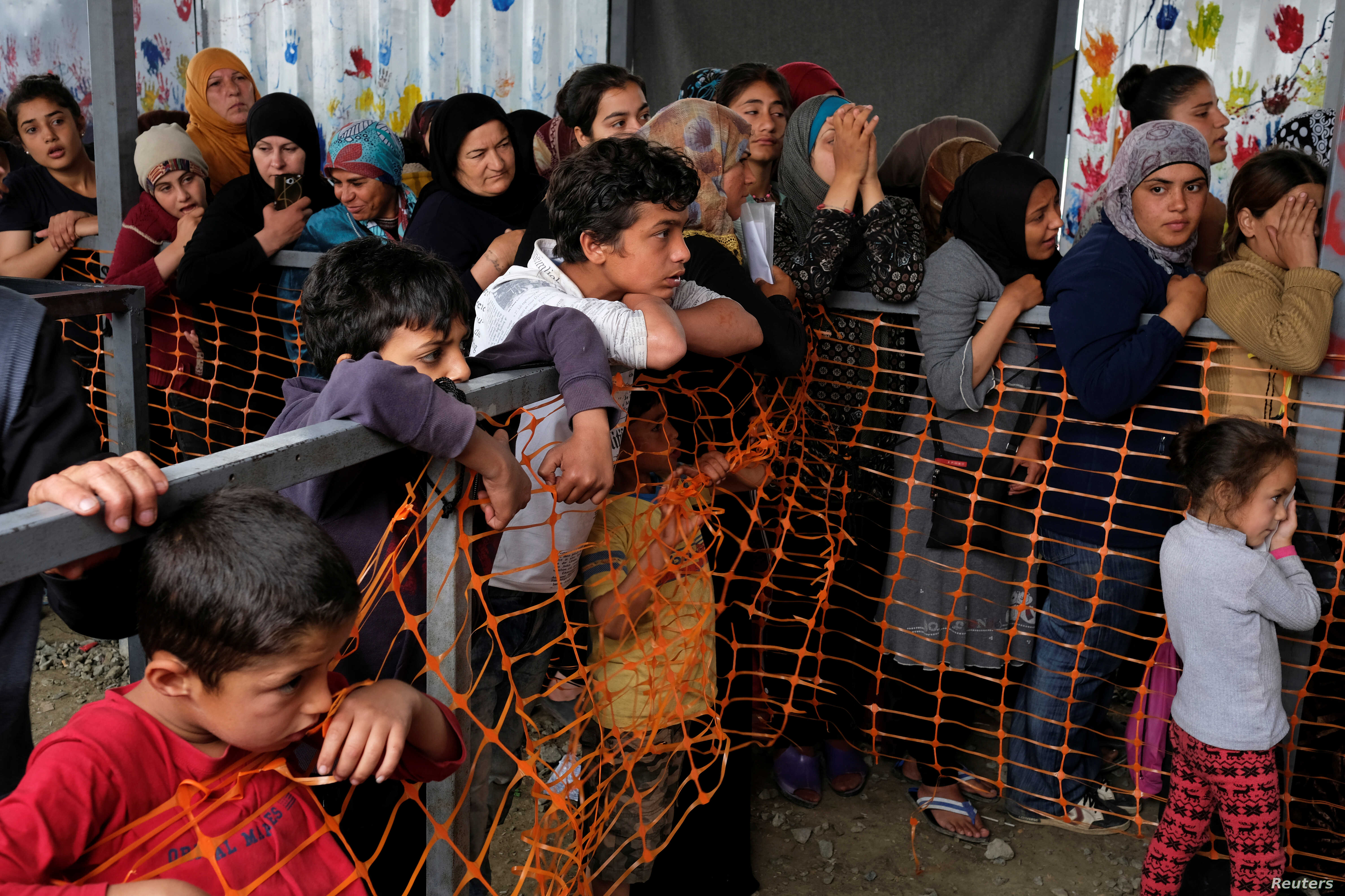 Children watch as women queue to receive free clothes at a makeshift camp for refugees and migrants at the Greek-Macedonian border near the village of Idomeni, Greece, May 12, 2016.