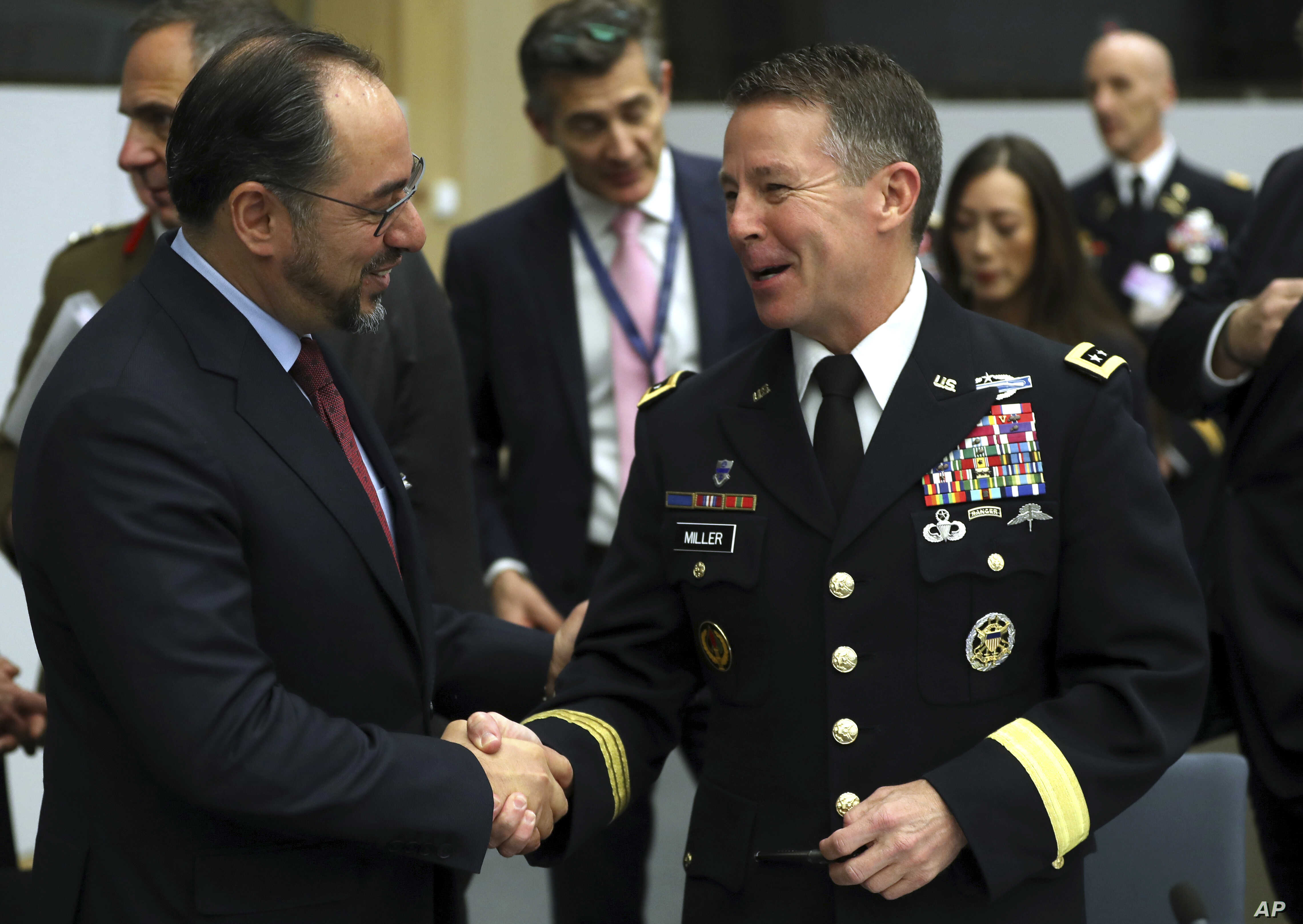 Resolute Support Mission Commander, U.S. Army General Austin Scott Miller, right, shakes hands with Afghanistan's Foreign Minister Salahuddin Rabbani during a meeting of the North Atlantic Council and Resolute Support at NATO headquarters in Brussels...