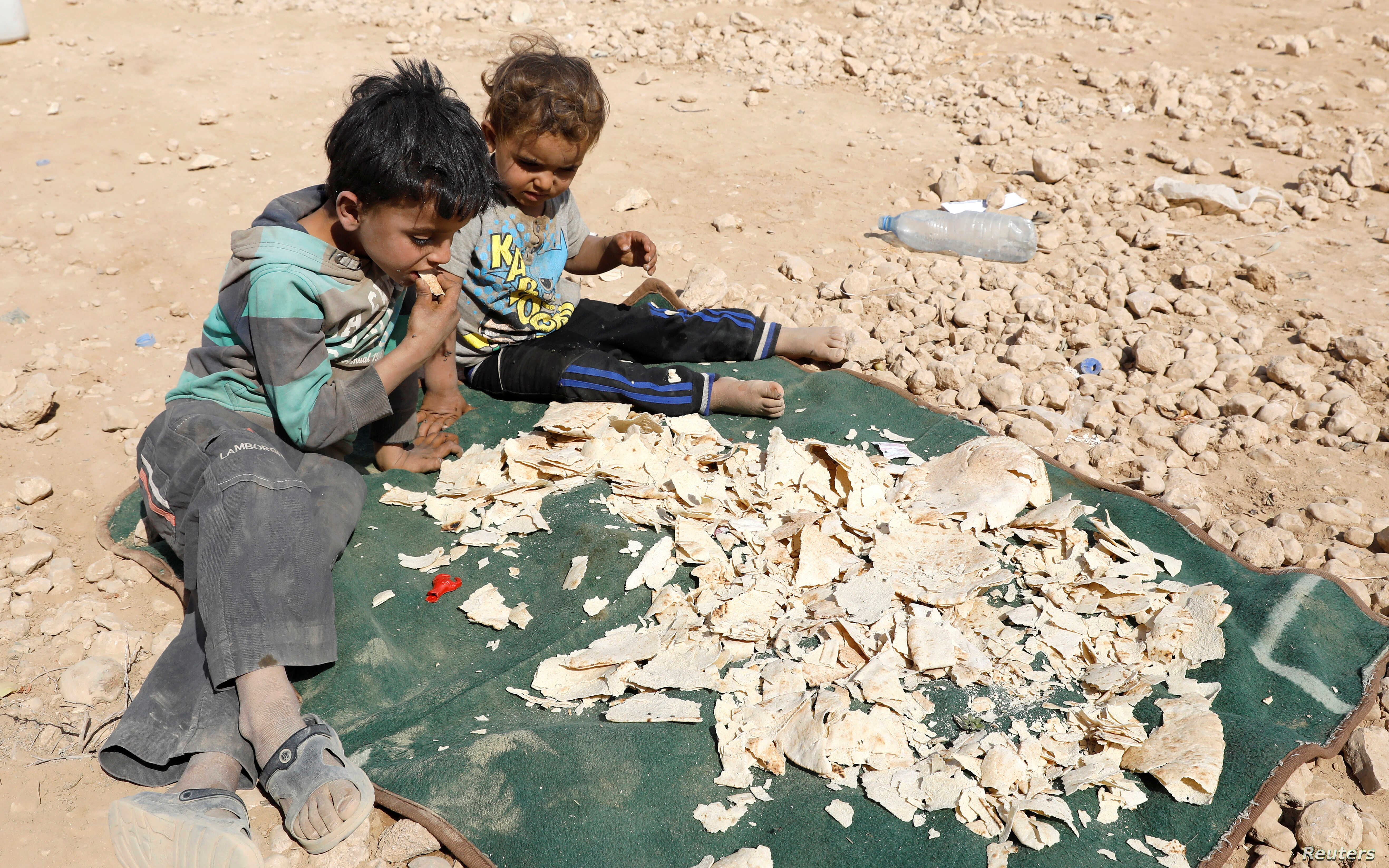 Children play near stale bread being dried under the sun at a refugee camp for people displaced because of fighting between the Syrian Democratic Forces and Islamic State militants, in Ain Issa, Syria, Oct. 14, 2017.