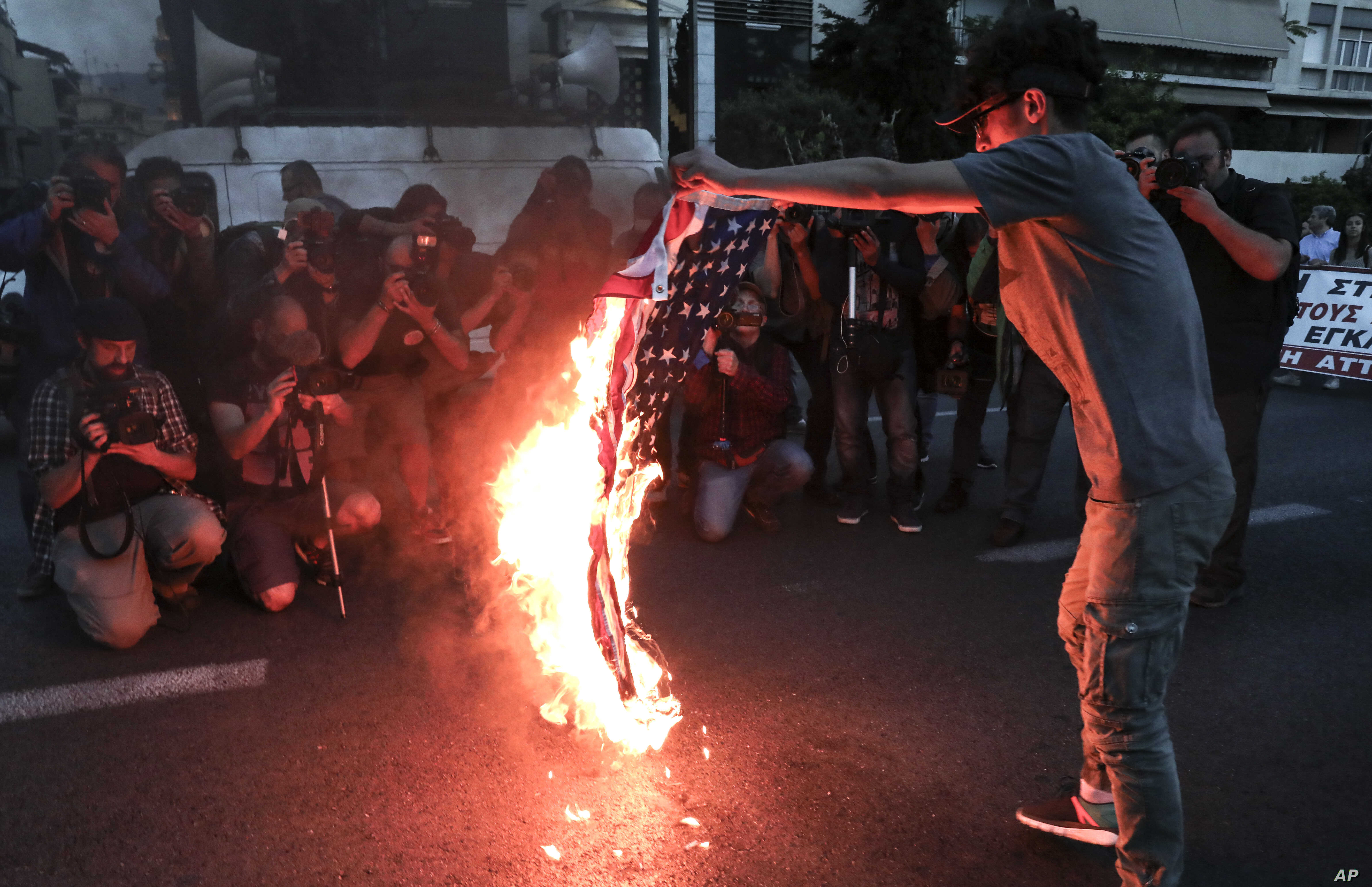 A protester holds a burning U.S. flag during a rally outside the U.S. embassy in Athens, Saturday, April 14, 2018.