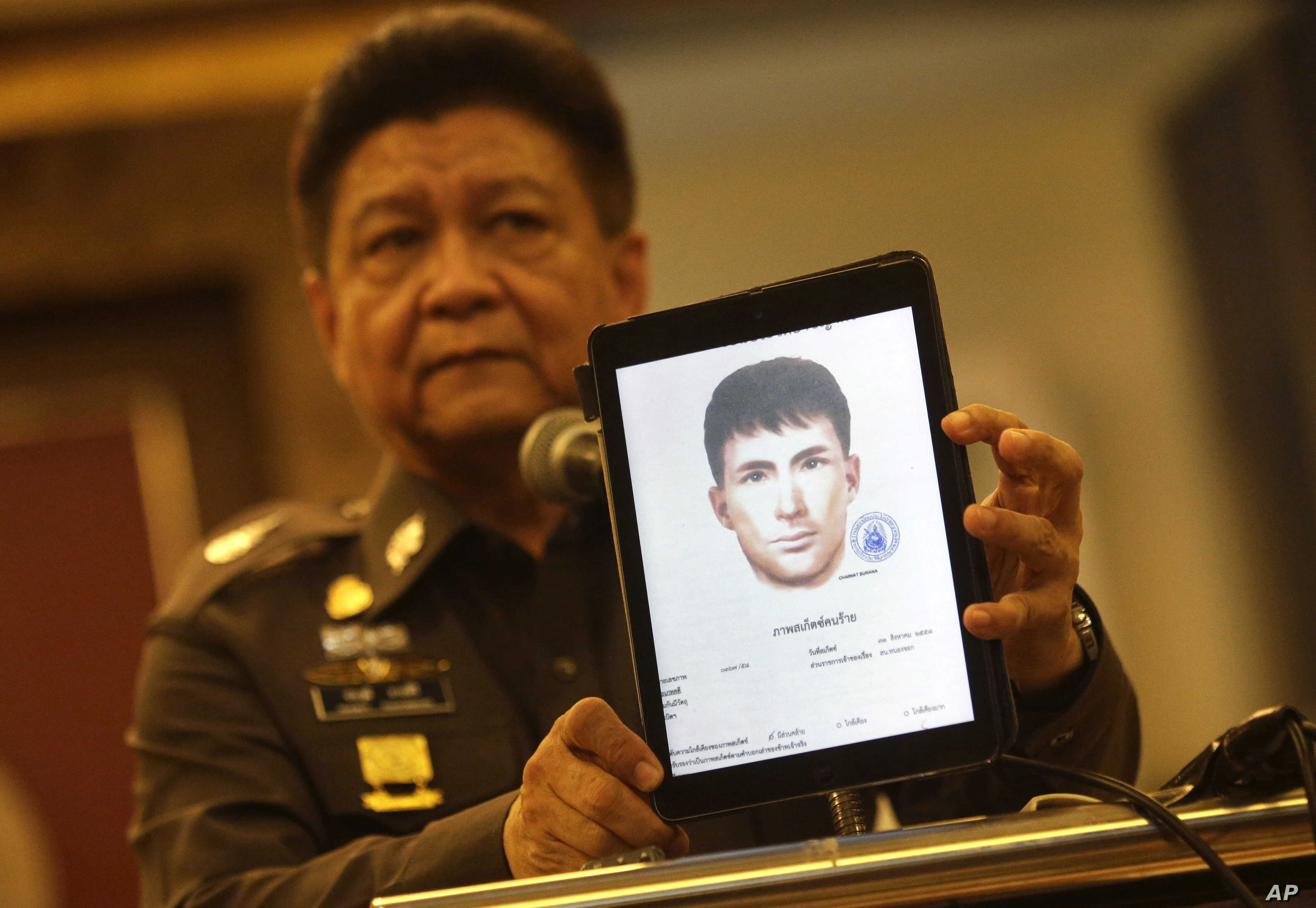 Police spokesman Lt. Gen. Prawuth Thavornsiri shows a photo of one of three men Thai authorities have issued new arrest warrants for in connection with the bombing case, in Bangkok, Thailand, Sept. 1, 2015.