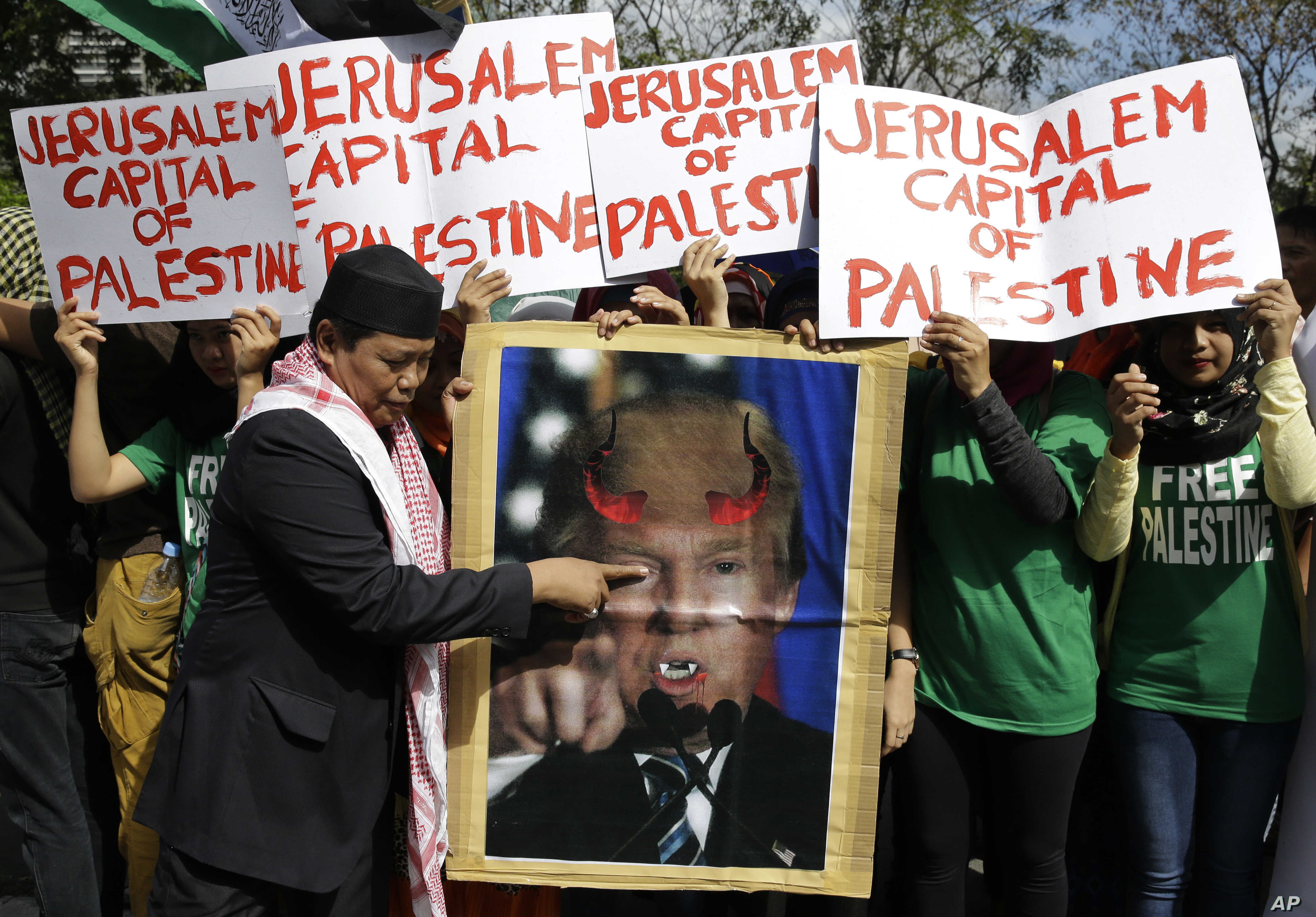 FILE - A Muslim protester plays with a portrait of U.S. President Donald Trump with horns and fangs as they try to march toward the Israel Embassy to protest against Trump's decision to recognize Jerusalem as the capital of Israel in metropolitan Man...