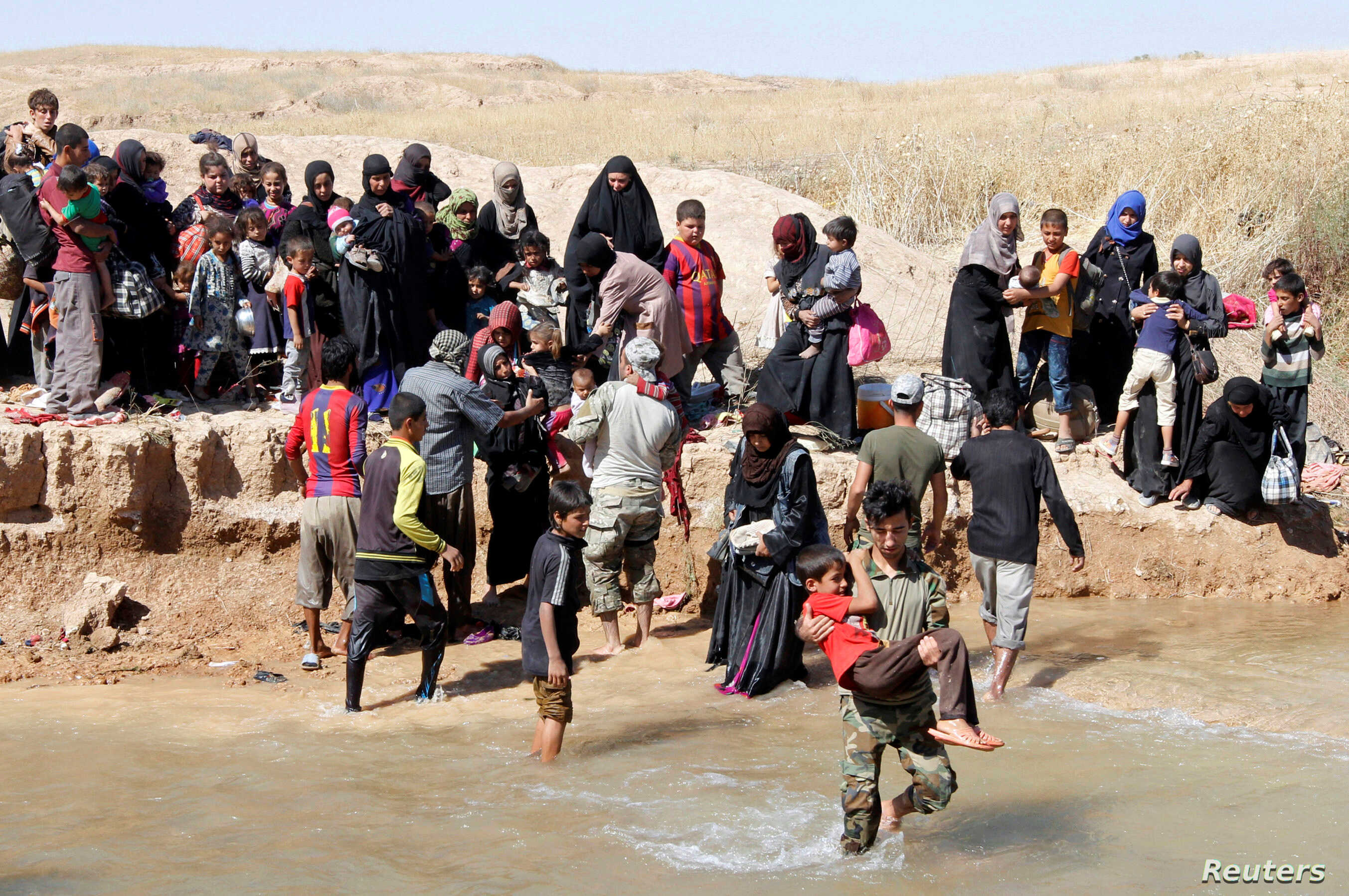 Displaced people, who fled from their homes in Hawija, cross the water to reach the other bank to be transported to camps for displaced people, in southwest of Kirkuk, Iraq, Oct. 4, 2017.