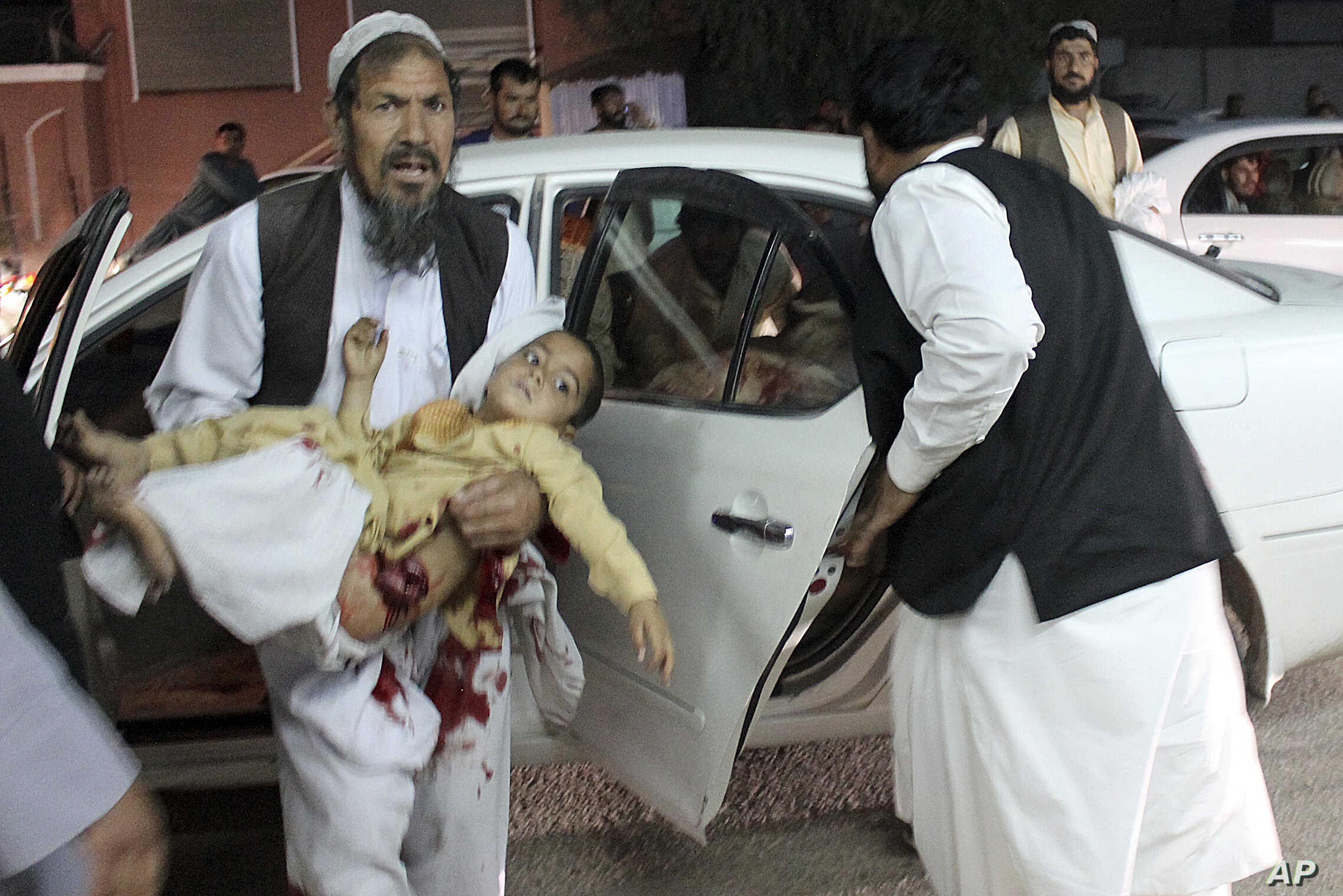 A man carries a wounded boy to a hospital after a car bombing outside a sports stadium in Lashkargah, capital city of southern Helmand province, Afghanistan, March 23, 2018. Provincial chief of police Abdul Ghafar Safi said the blast was carried out ...