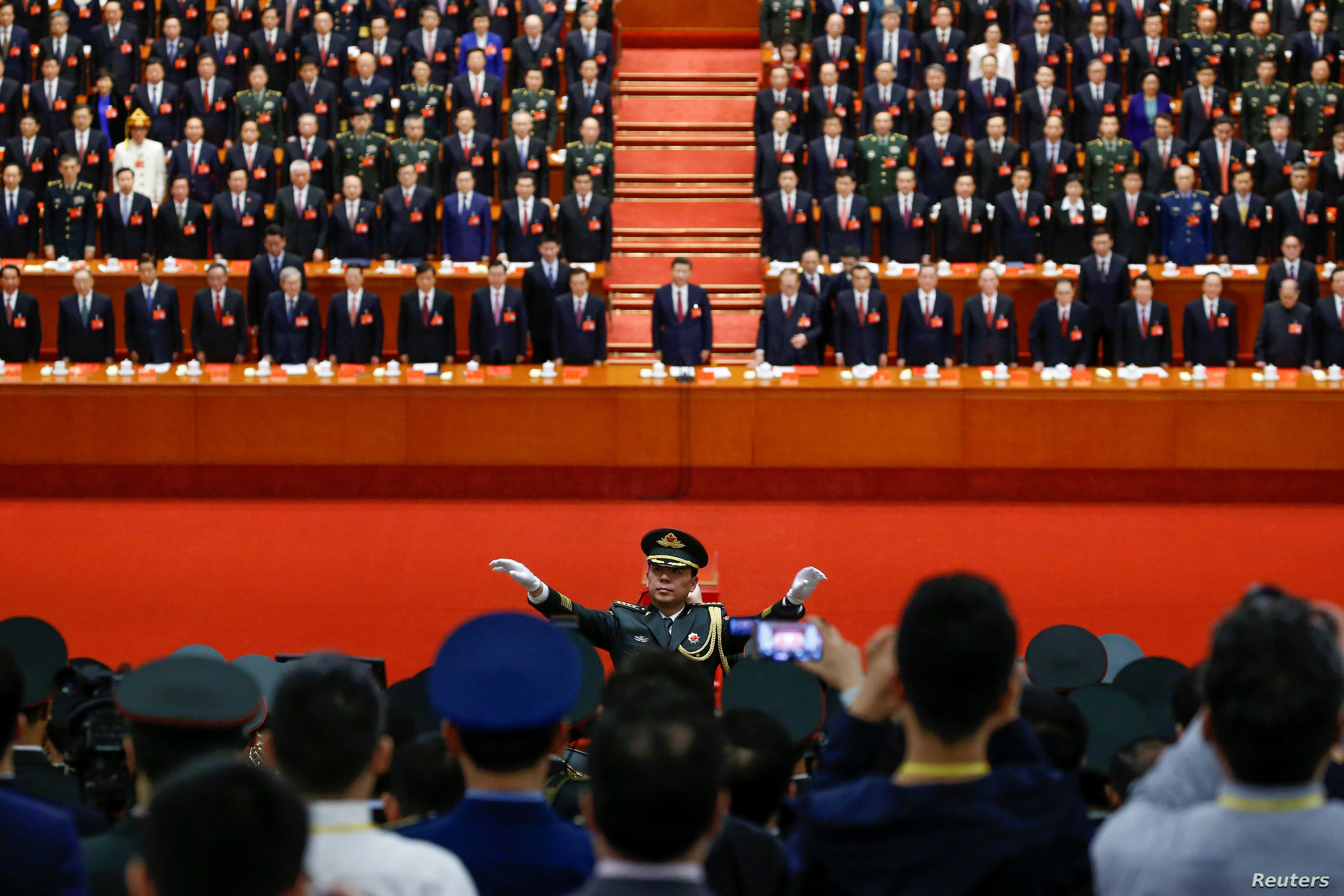 A conductor leads an orchestra as delegates stand for the national anthem during the closing session of the 19th National Congress of the Communist Party of China at the Great Hall of the People in Beijing, Oct. 24, 2017.