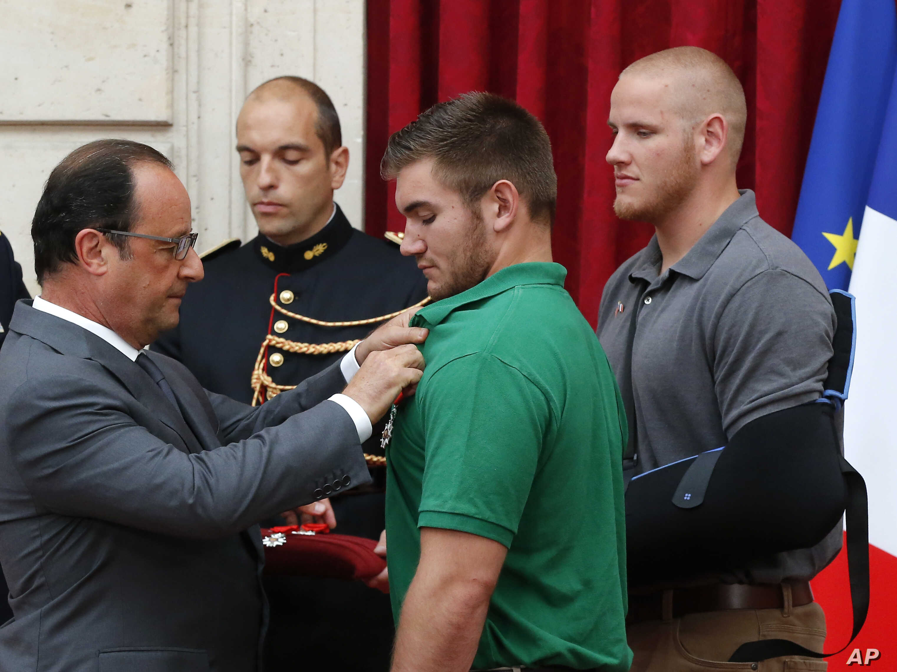 French President Francois Hollande, left, awards with the Legion of Honor Alek Skarlatos a U.S. National Guardsman from Roseburg, Oregon, while  U.S. Airman Spencer Stone, right, looks on at the Elysee Palace, Monday Aug.24, 2015 in Paris, France.