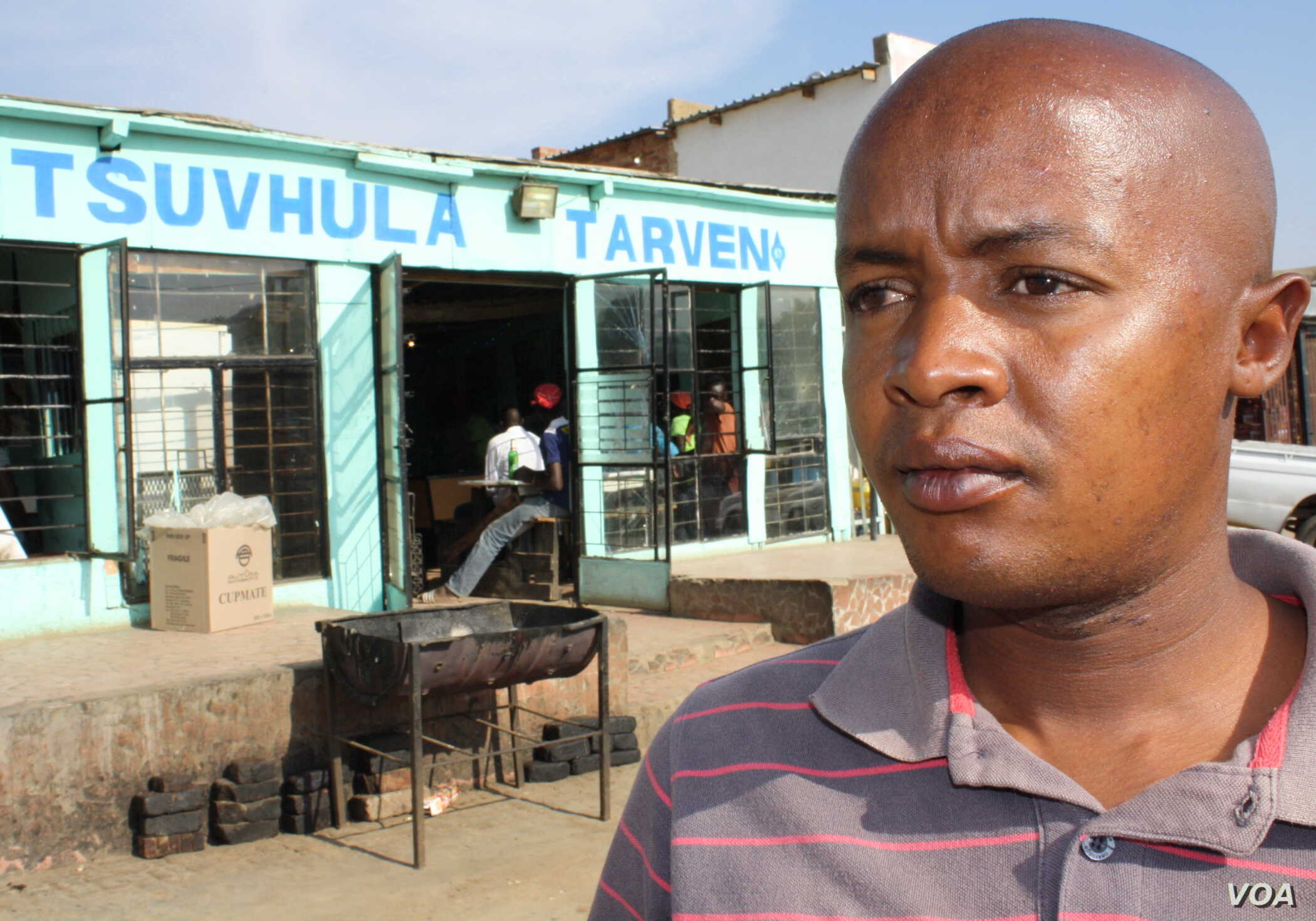 """Community health care worker Brown Lekekela stands outside a tavern in a township in South Africa, where young women often meet older men with whom they have dangerous """"transactional"""" sexual relationships. (D. Taylor/VOA)"""