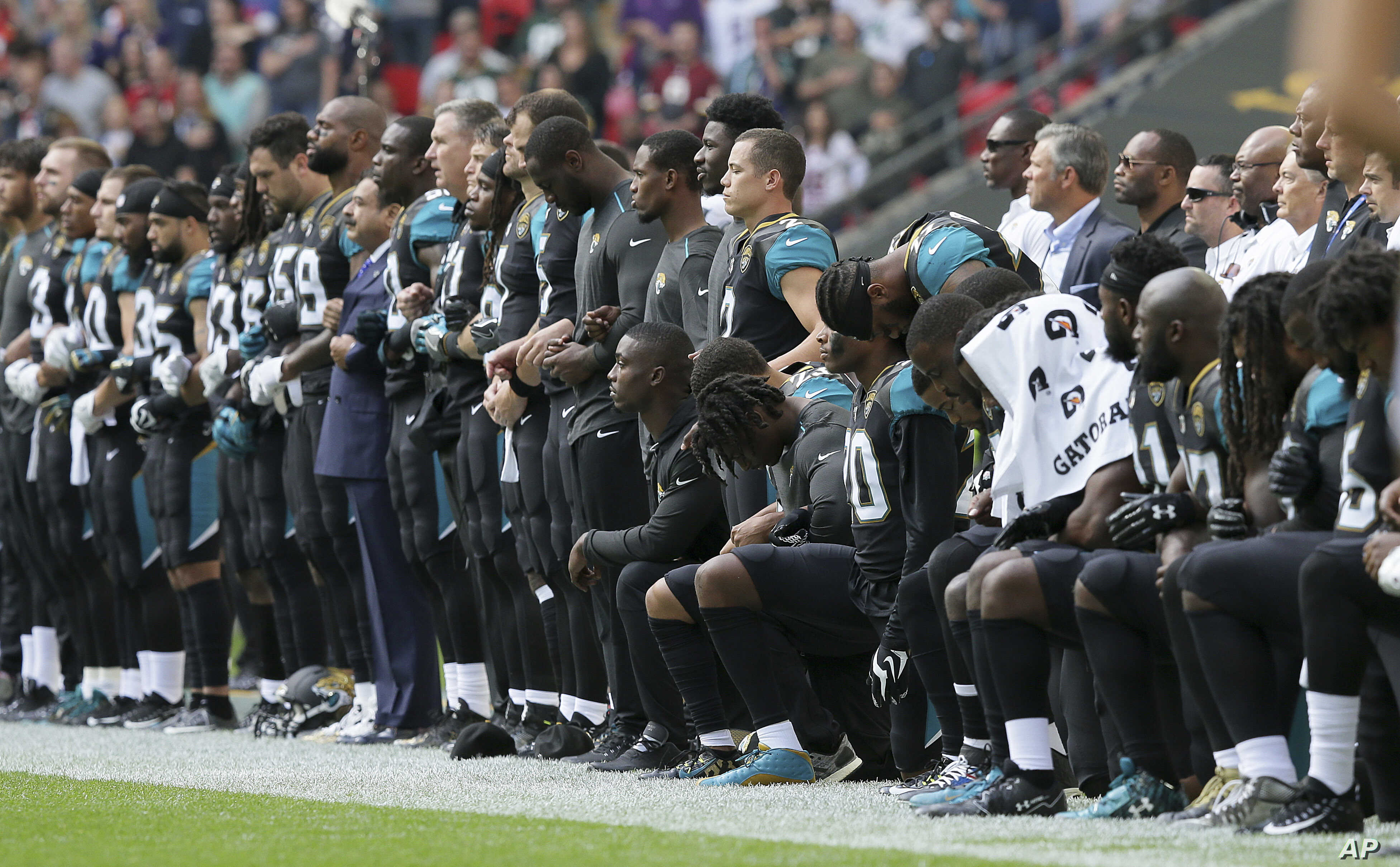 a4ef4b210f1 Jacksonville Jaguars players lock arms and kneel down during the playing of  the U.S. national anthem before an NFL football game against the Baltimore  ...