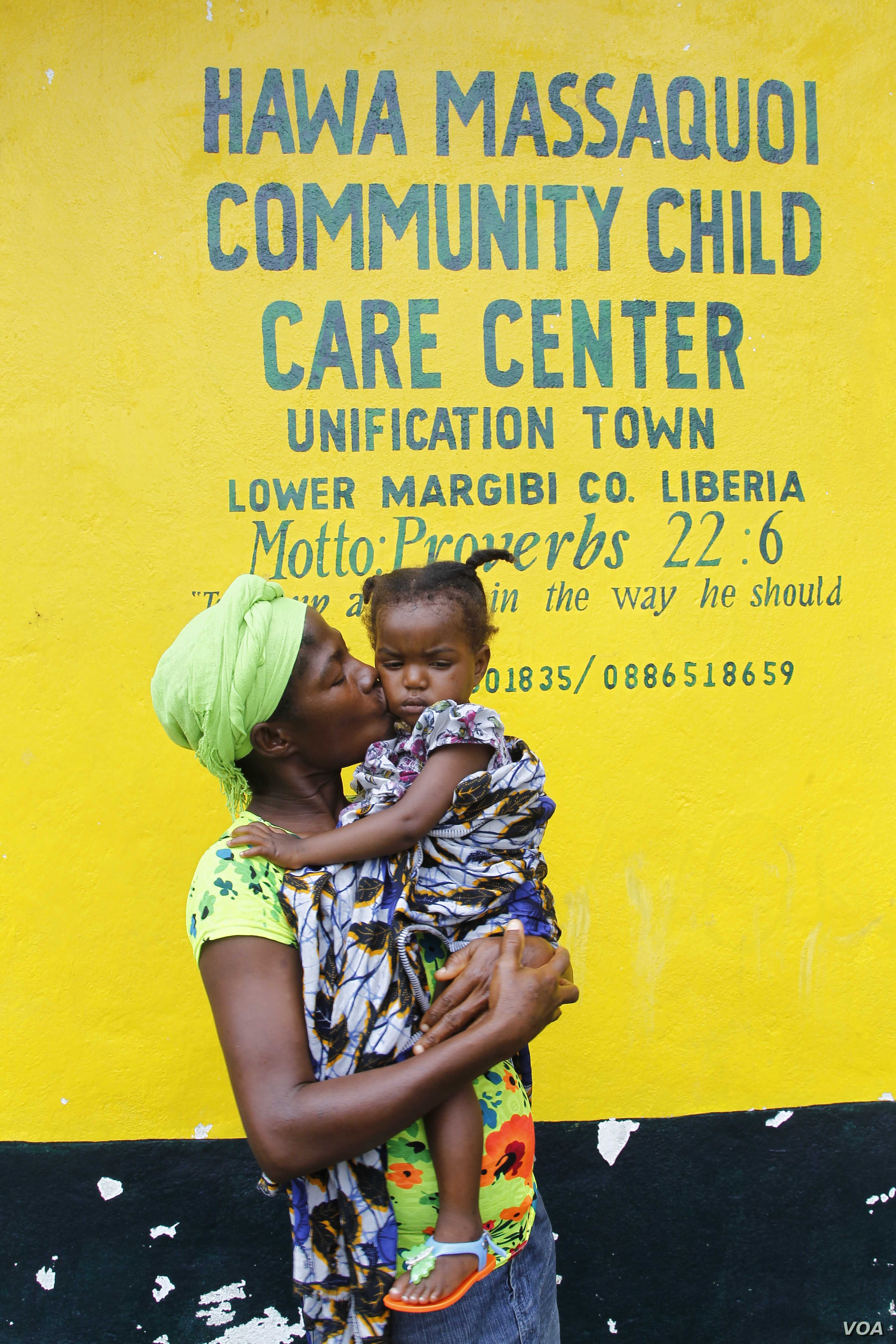 Mamie Harris, a caregiver at Liberia's Hawa Massaquoi transit center in Unification Town, Margibi County, holds 18-month-old Agnes. The center, run by the government with UNICEF support, aids children affected by Ebola. (© UNICEF /Jallanzo)