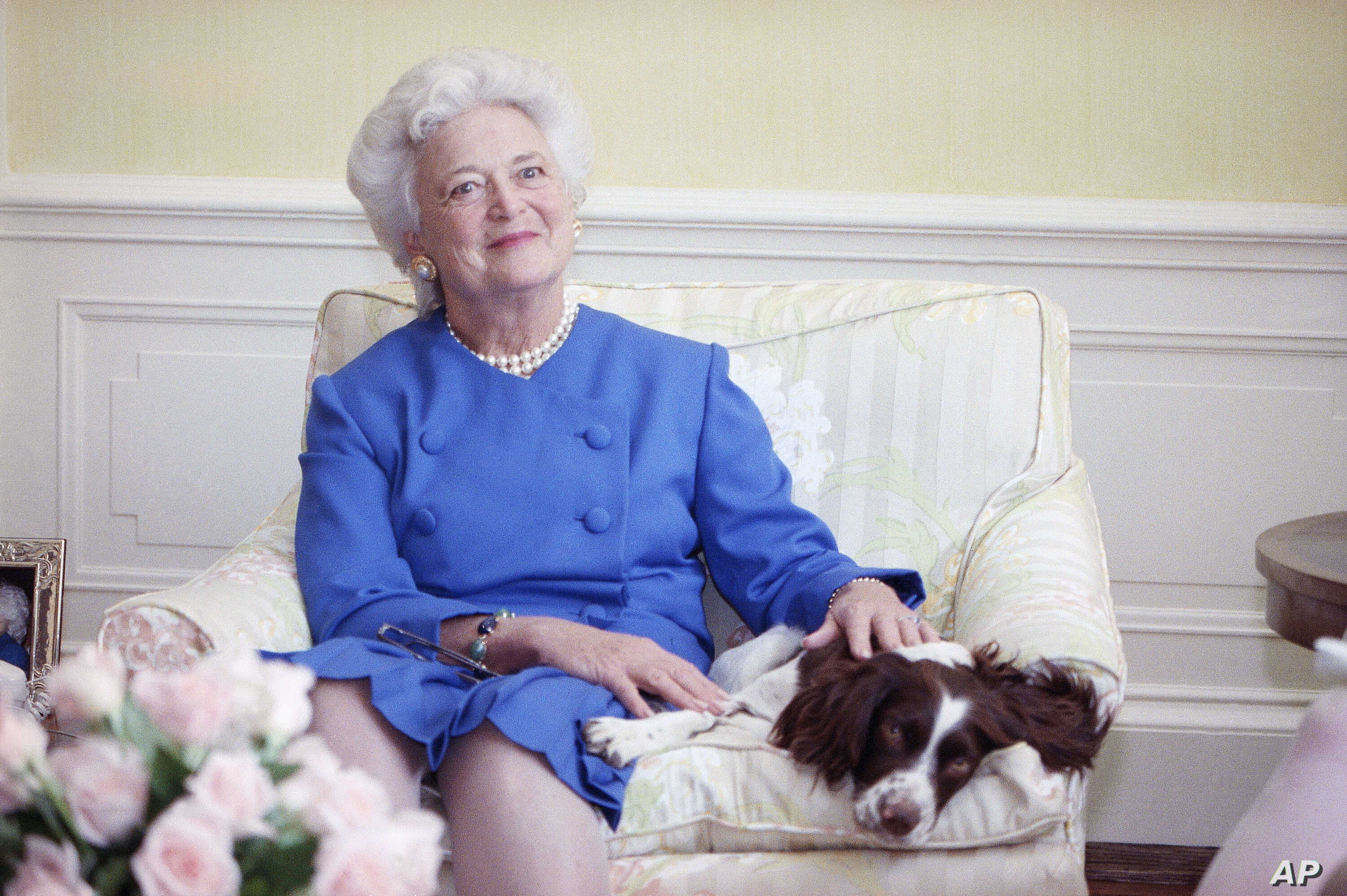 First lady Barbara Bush poses with her dog Millie in 1990.