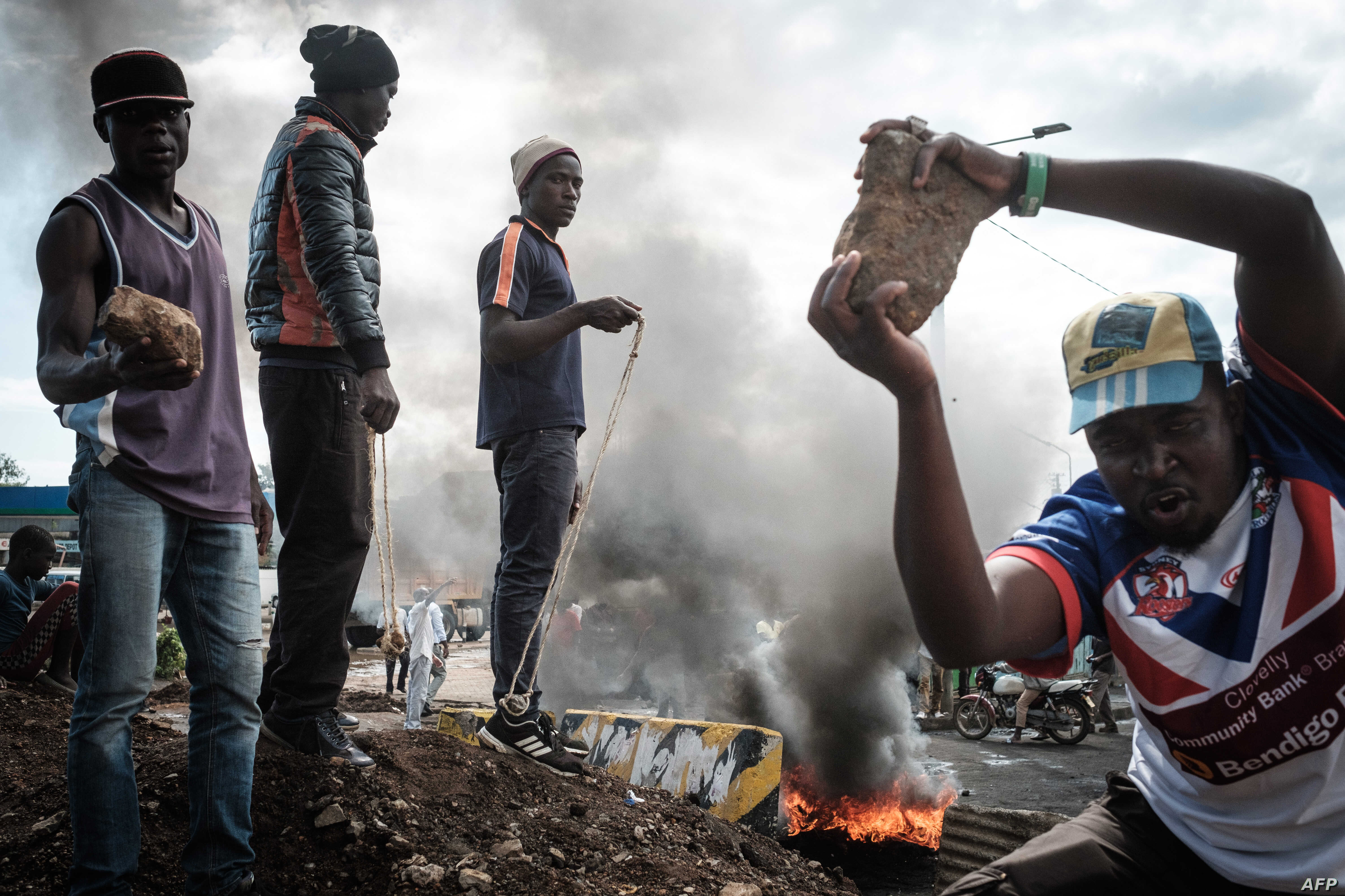 Opposition supporters hold up bricks as they block streets and burn tires during a protest in Kisumu, Kenya, on Oct. 11, 2017.