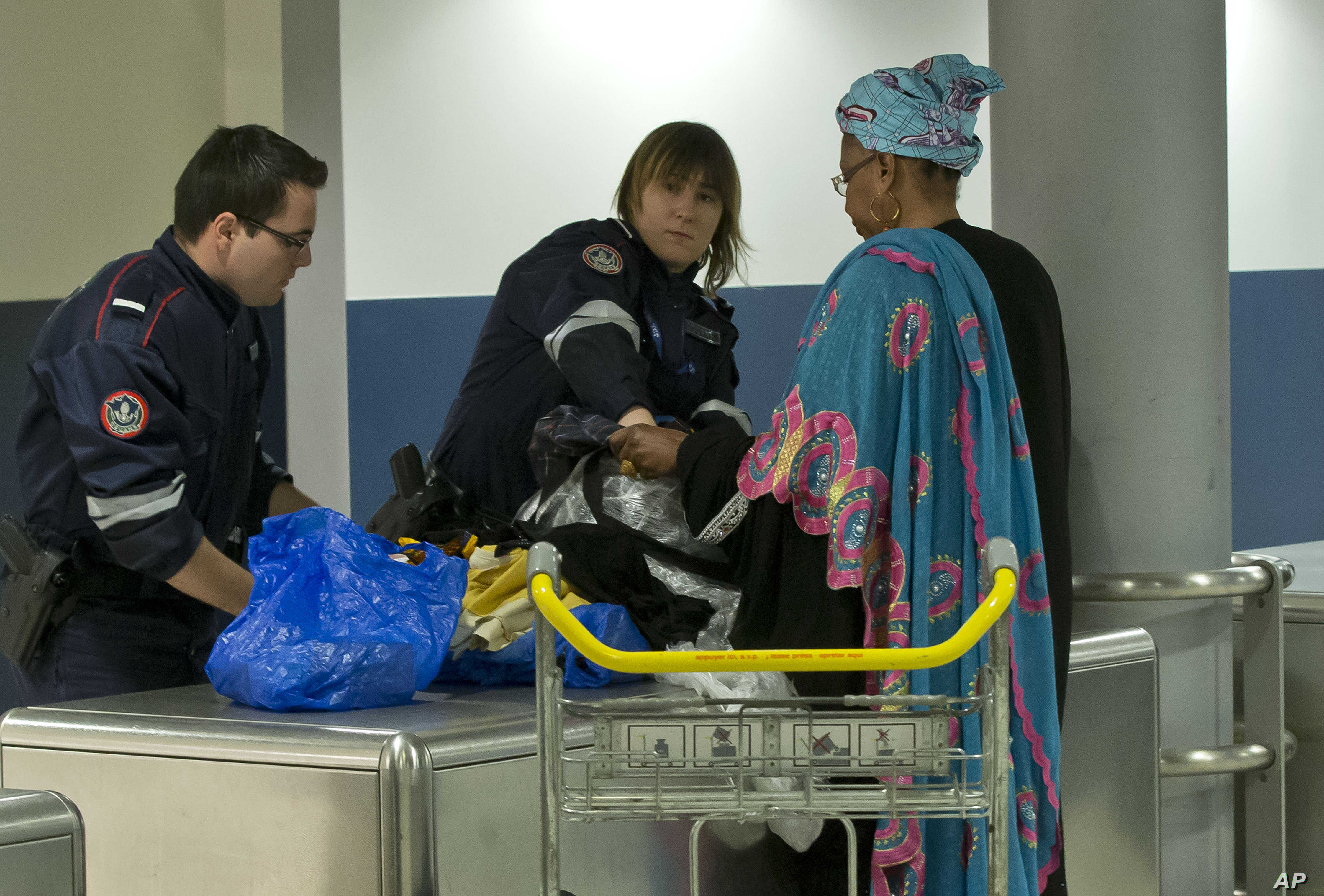 FILE - Custom officers check the luggage of a passenger at Charles de Gaulle airport, in Roissy, north of Paris, March 23, 2016.