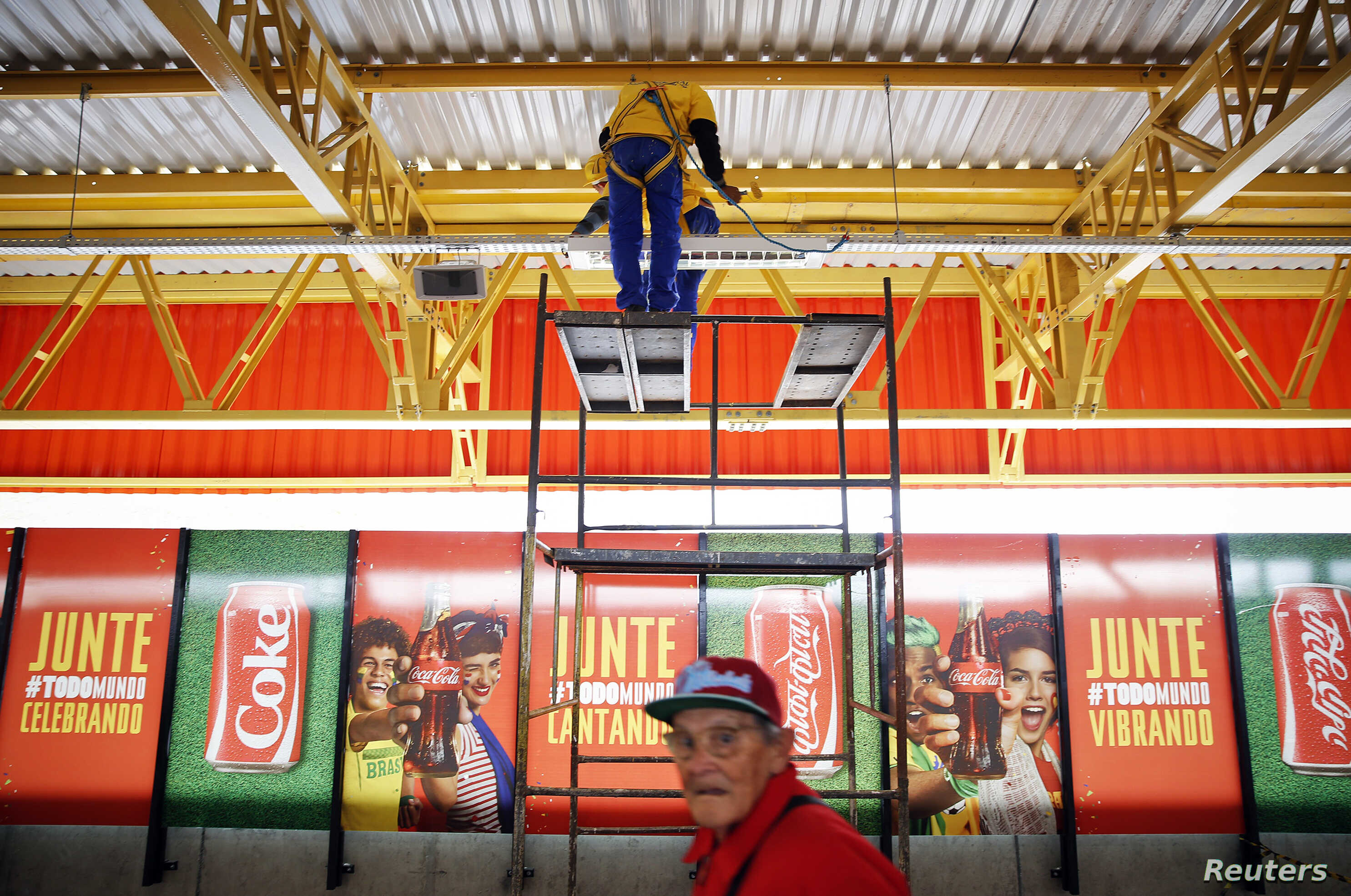 FILE - Workers fix lighting above advertising posters of FIFA sponsors outside a metro station near the World Cup stadium in Sao Paulo.