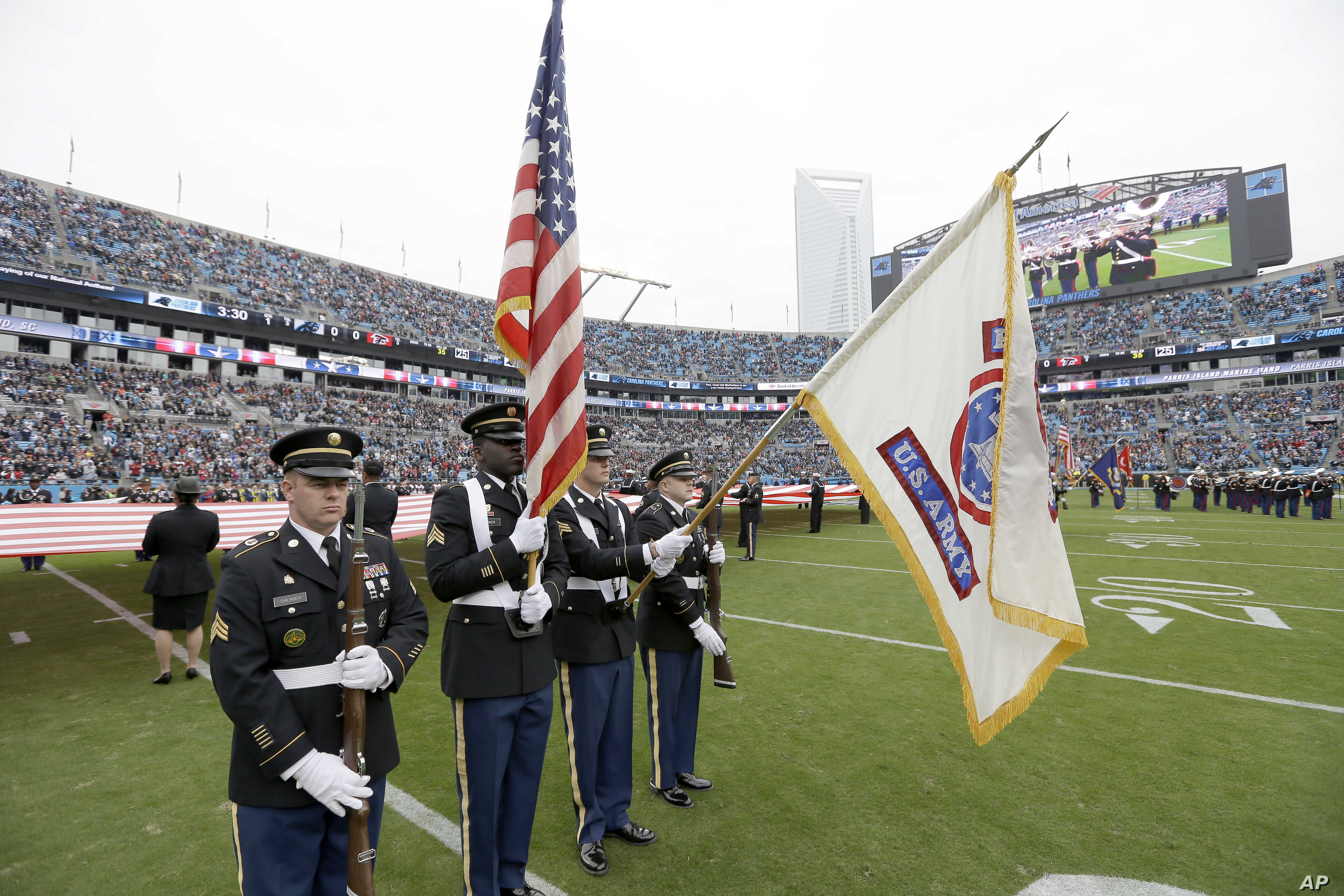 FILE - Members of the U.S. Army color guard join color guards from other military services for the National Anthem before an NFL football game between the Atlanta Falcons and Carolina Panthers in Charlotte, N.C., Nov. 16, 2014.