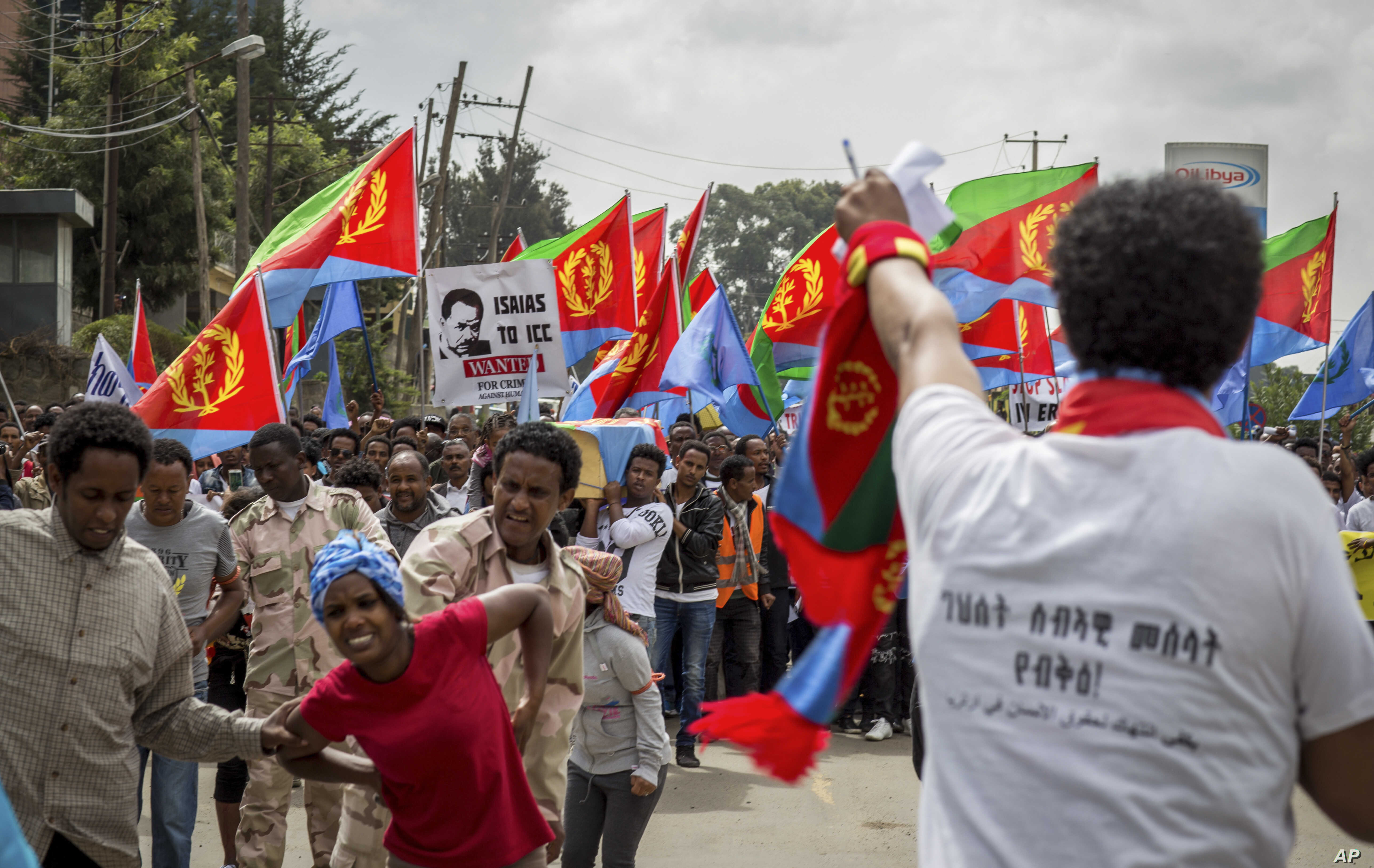 FILE - Eritrean exiles, some holding Eritrean flags and some dressed as Eritrean military members, simulating beatings and torture, left, rally outside African Union headquarters, in Addis Ababa, Ethiopia, June 23, 2016.
