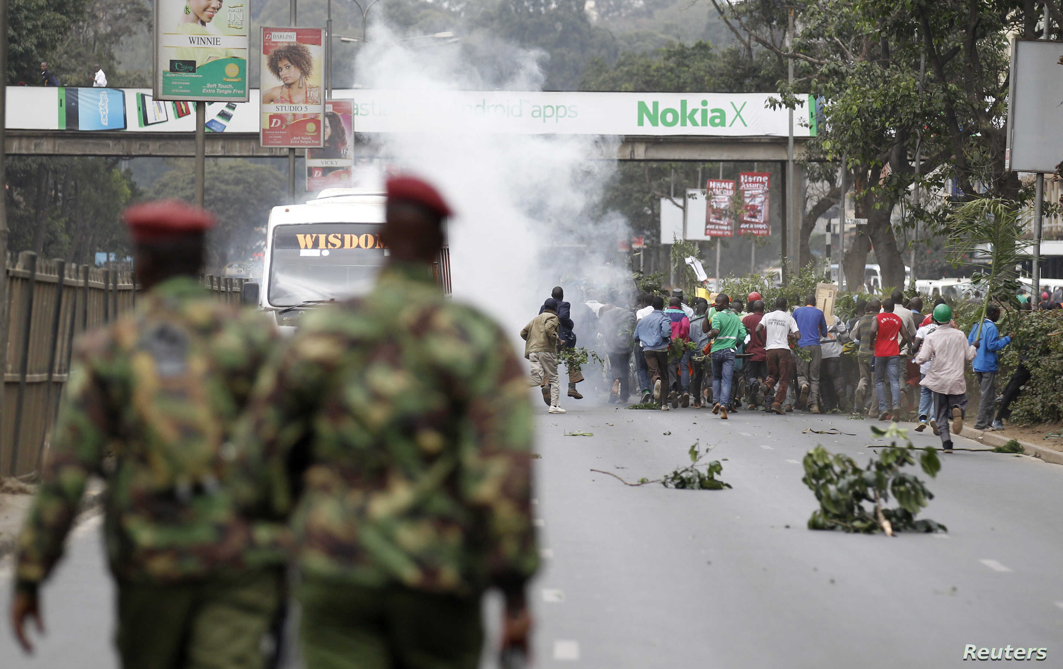 """Supporters of Kenya's opposition Coalition for Reforms and Democracy (CORD) run after riot police fired tear gas before their """"Saba Saba Day"""" rally at the Uhuru park grounds in the capital Nairobi, July 7, 2014."""
