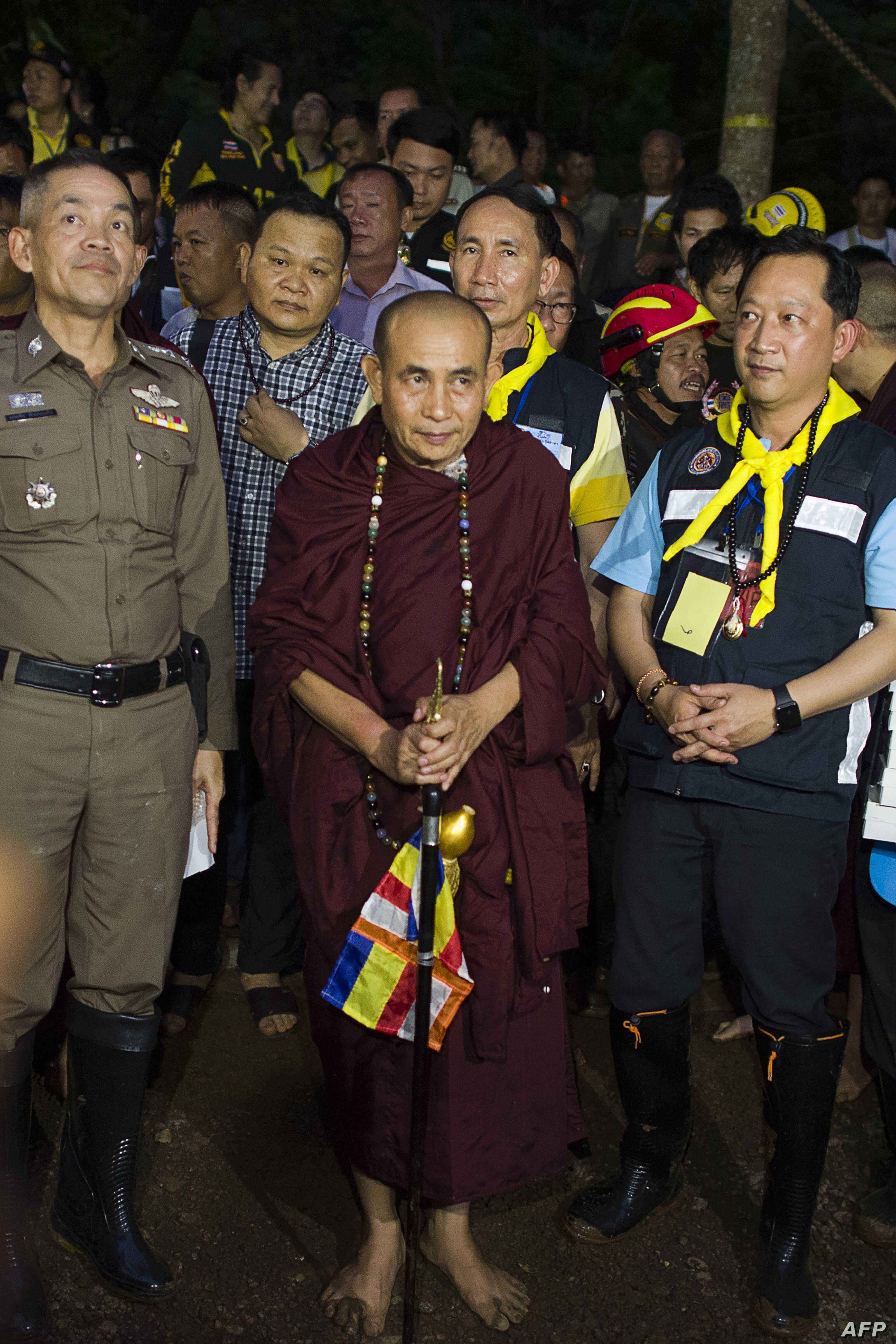 Buddhist monk Kruba Boonchum, center, exits after praying with relatives of the missing children in Tham Luang cave during a rescue operation for 12 boys and their coach trapped in the cave at the Khun Nam Nang Non Forest Park in the Mae Sai district...