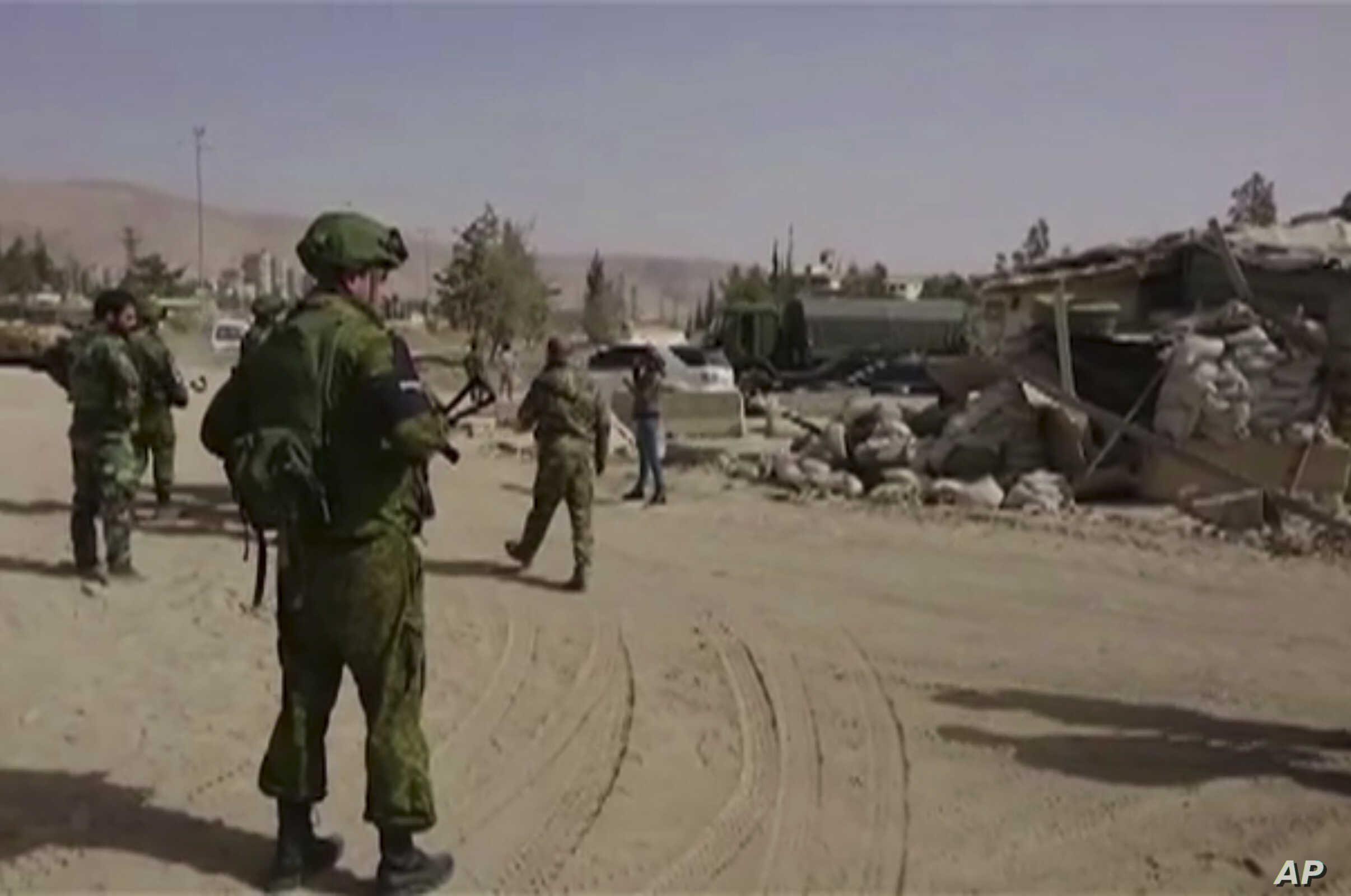FILE - In this is image from video, Syrian government forces and Russian soldiers oversee the evacuation by buses of rebel fighters and their families, at a checkpoint in eastern Gouta, Syria, March, 22, 2108.