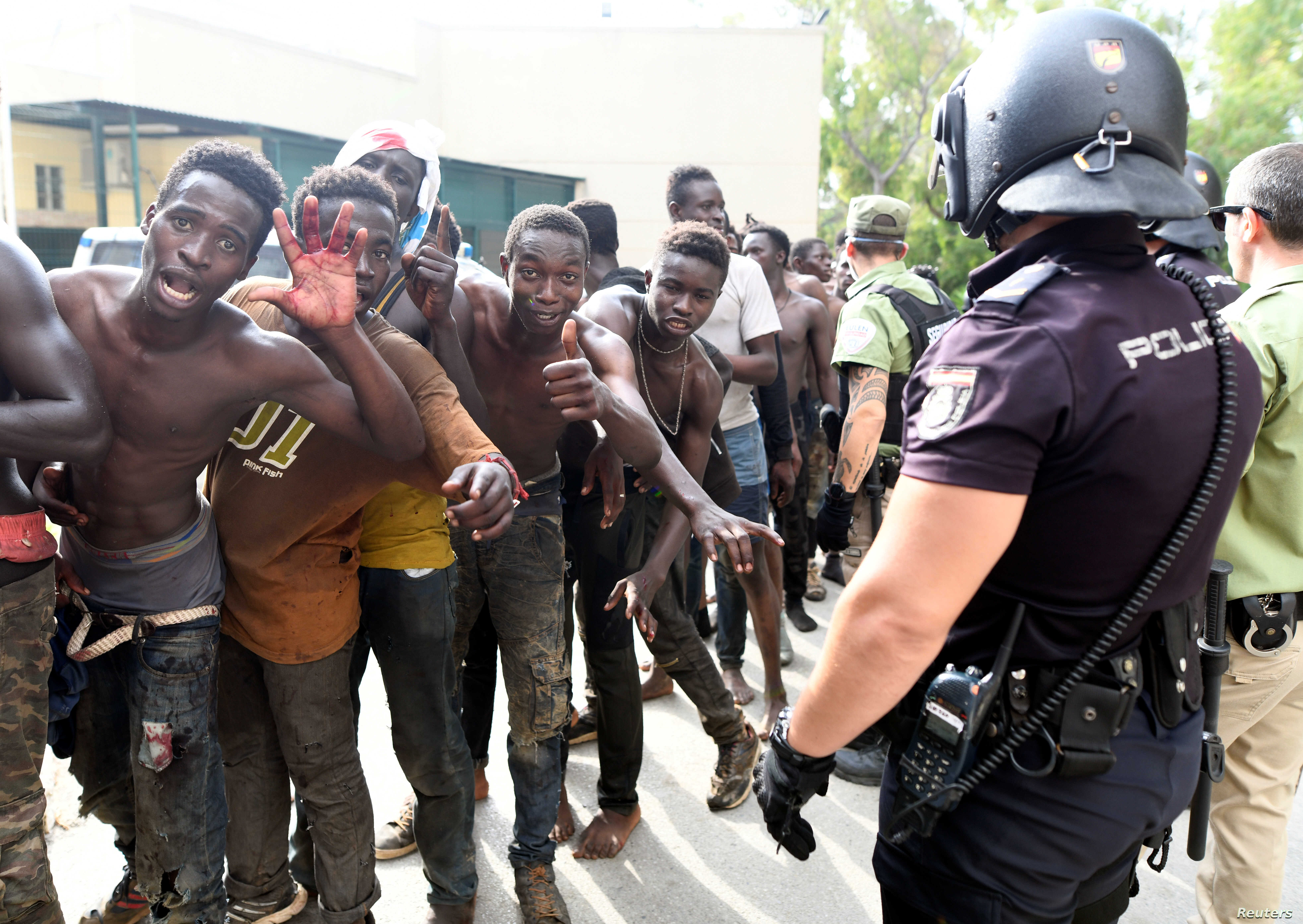 African immigrants celebrate as they enter the immigrant center CETI in the Spanish enclave Ceuta, after some 200 refugees crossed the border fence between Morocco and Ceuta, Aug. 22, 2018