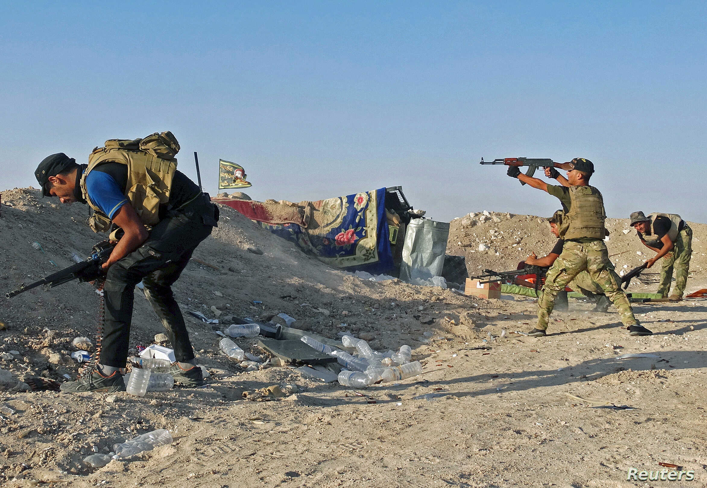 Iraqi security forces fire their weapons during clashes with Islamic State militants on the outskirts of Ramadi, June 15, 2015.
