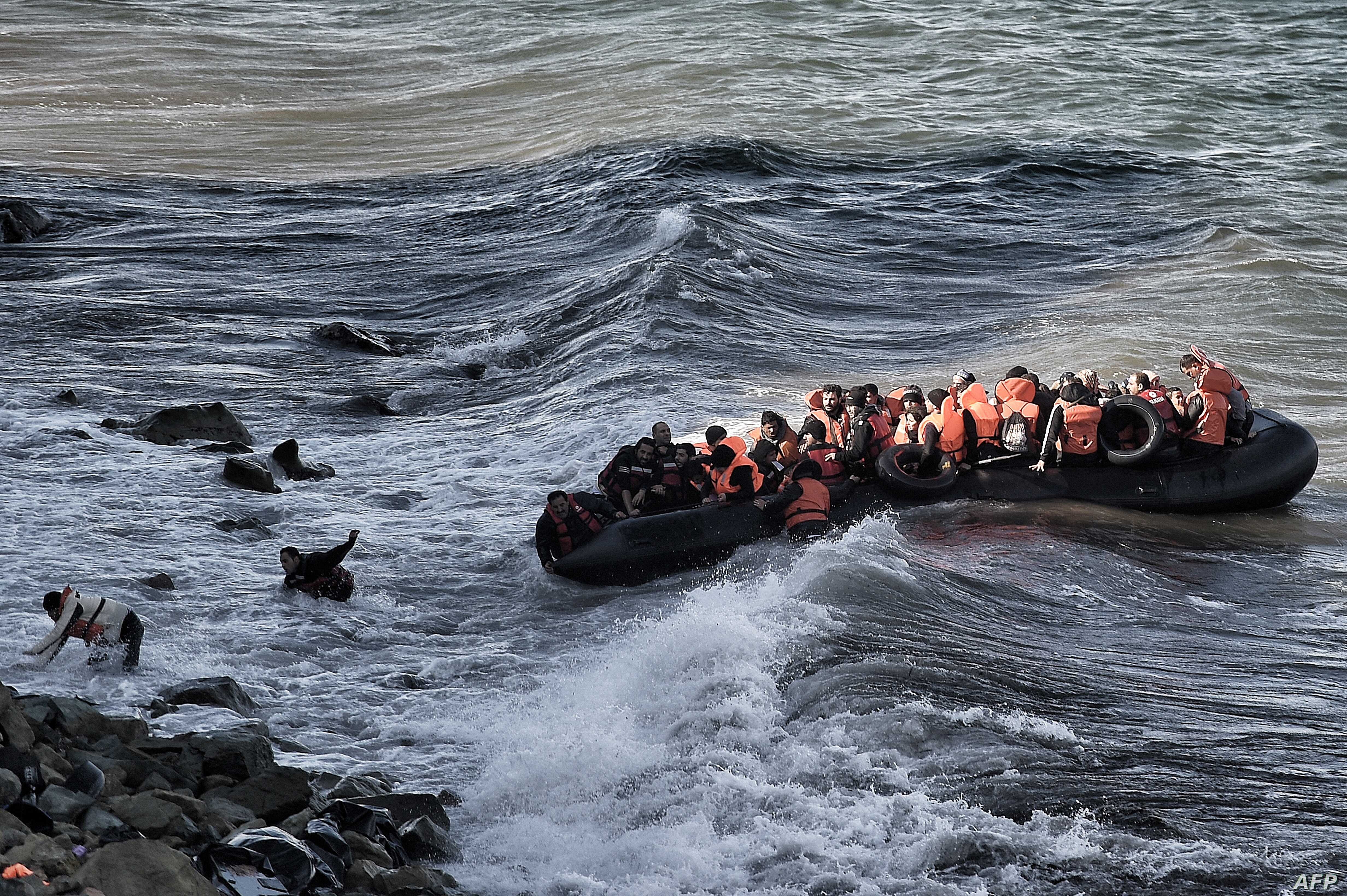 Refugees and migrants try to reach the shore on the Greek island of Lesbos, despite a rough sea, after crossing the Aegean Sea from Turkey, Oct. 30, 2015..