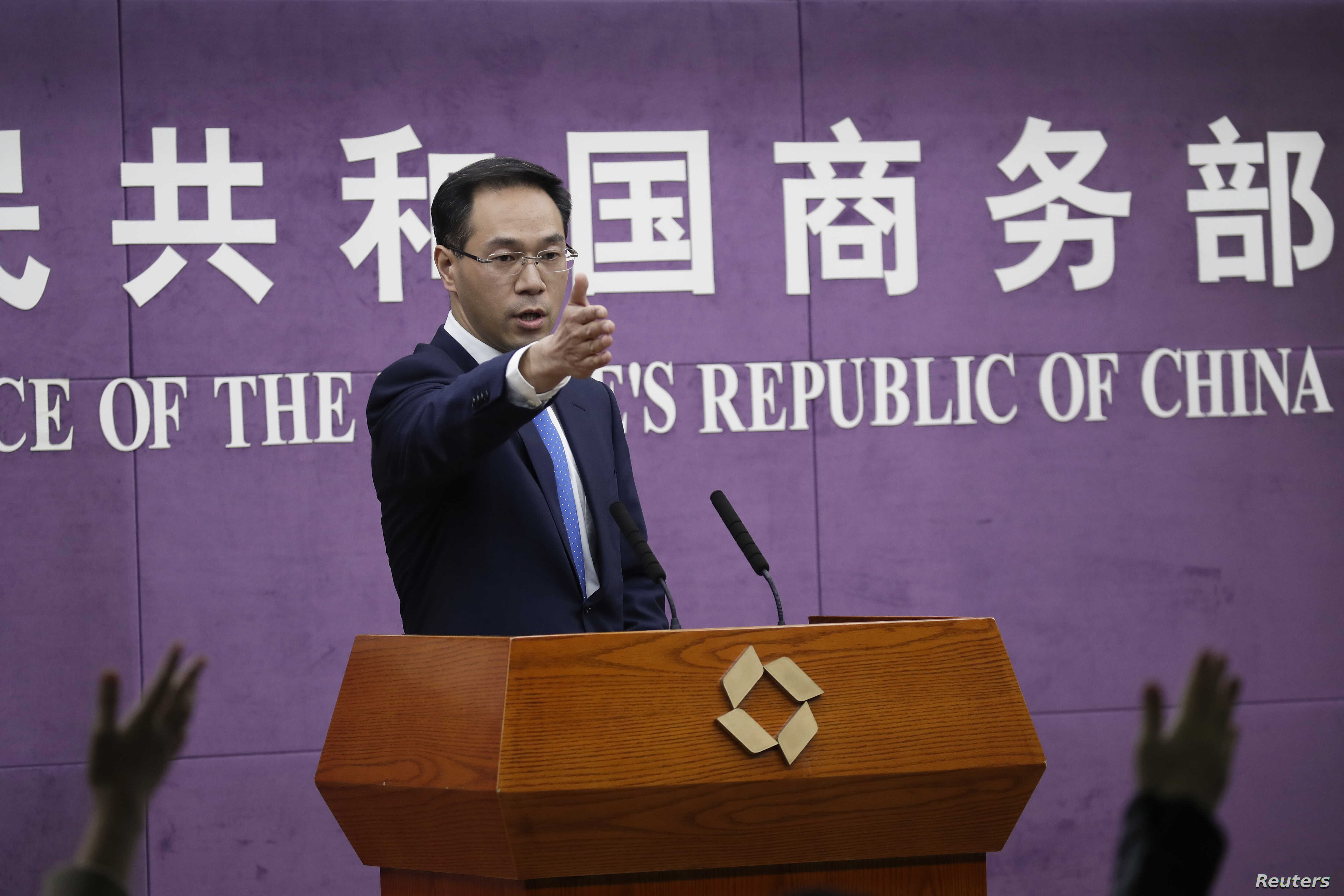 Chinese Ministry of Commerce spokesman Gao Feng gestures as journalists raise hands for questions during a press conference at the Ministry of Commerce in Beijing, April 6, 2018.