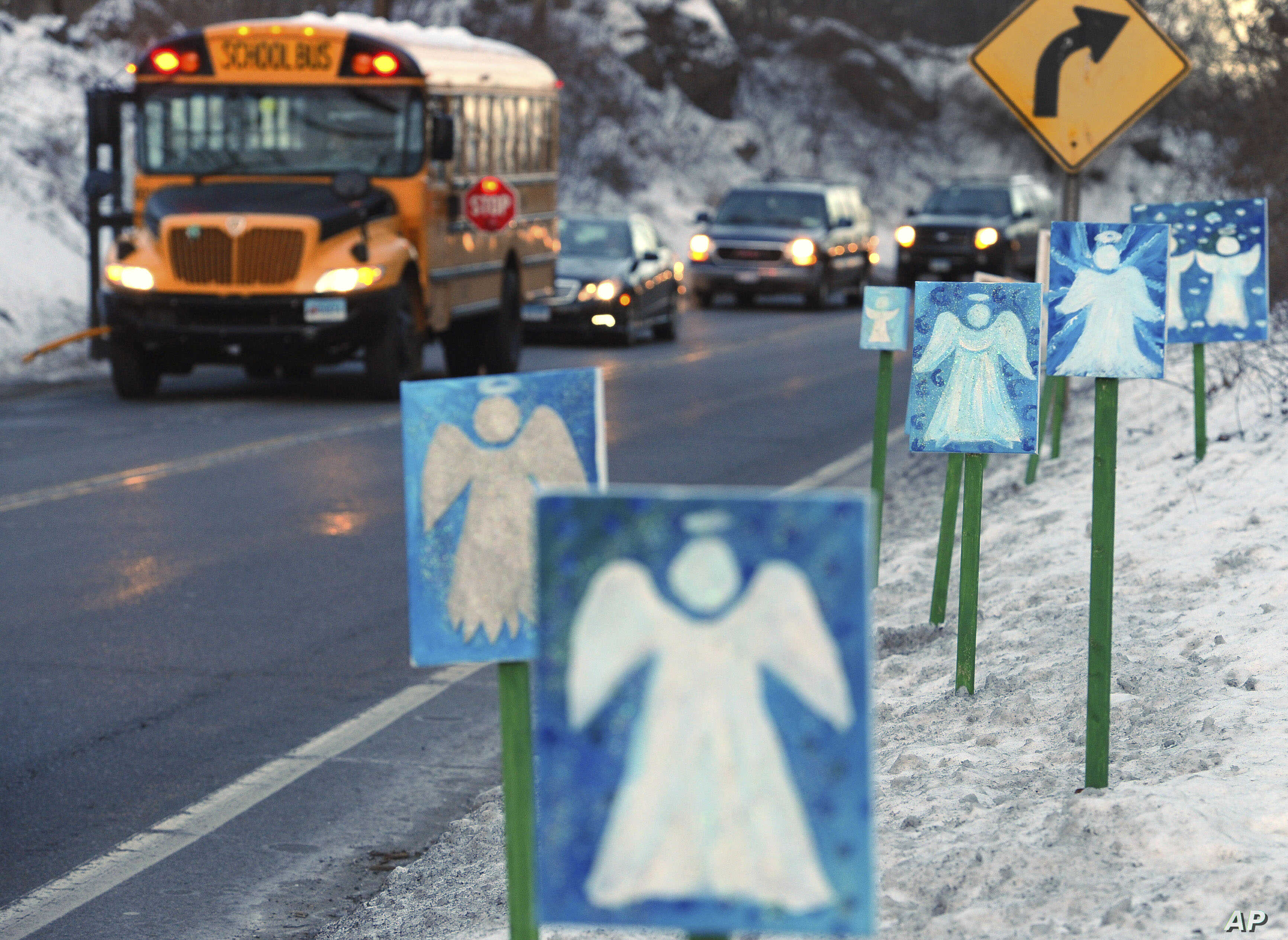 FILE - In this Jan. 3, 2013, file photo, a bus traveling from Newtown, Conn., to Monroe stops near 26 angel signs posted along the roadside in Monroe, Conn., on the first day of classes for Sandy Hook Elementary School students since the December 201...