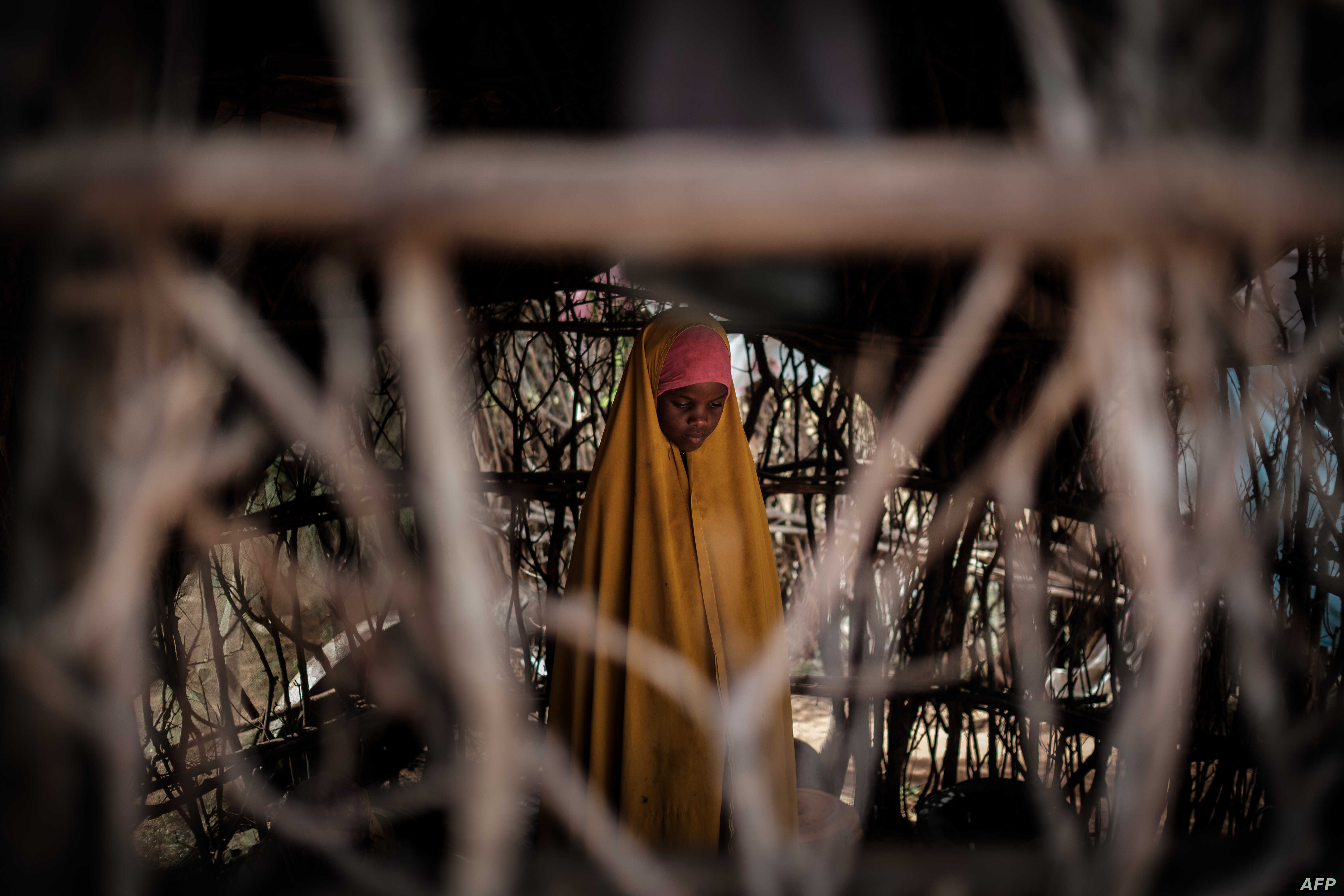 FILE - A Somali refugee girl stands in a makeshift shelter at Dadaab refugee complex, in the north-east of Kenya, on April 16, 2018.