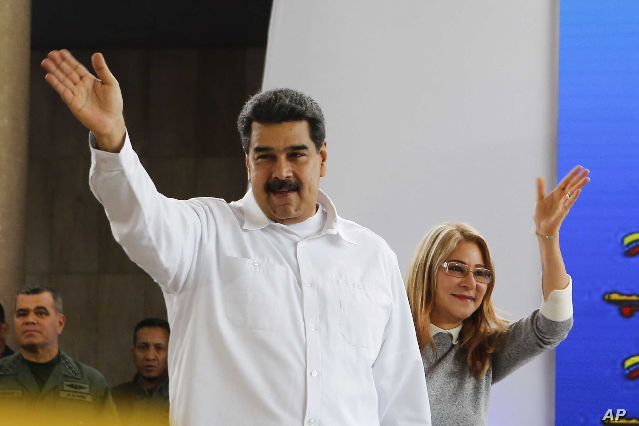 Venezuela's President Nicolas Maduro, left, and his wife Cilia Flores greet supporters upon their arrival to a meeting with Colombian citizens that reside in Venezuela, In Caracas, Venezuela, Tuesday, Sept. 25, 2018.
