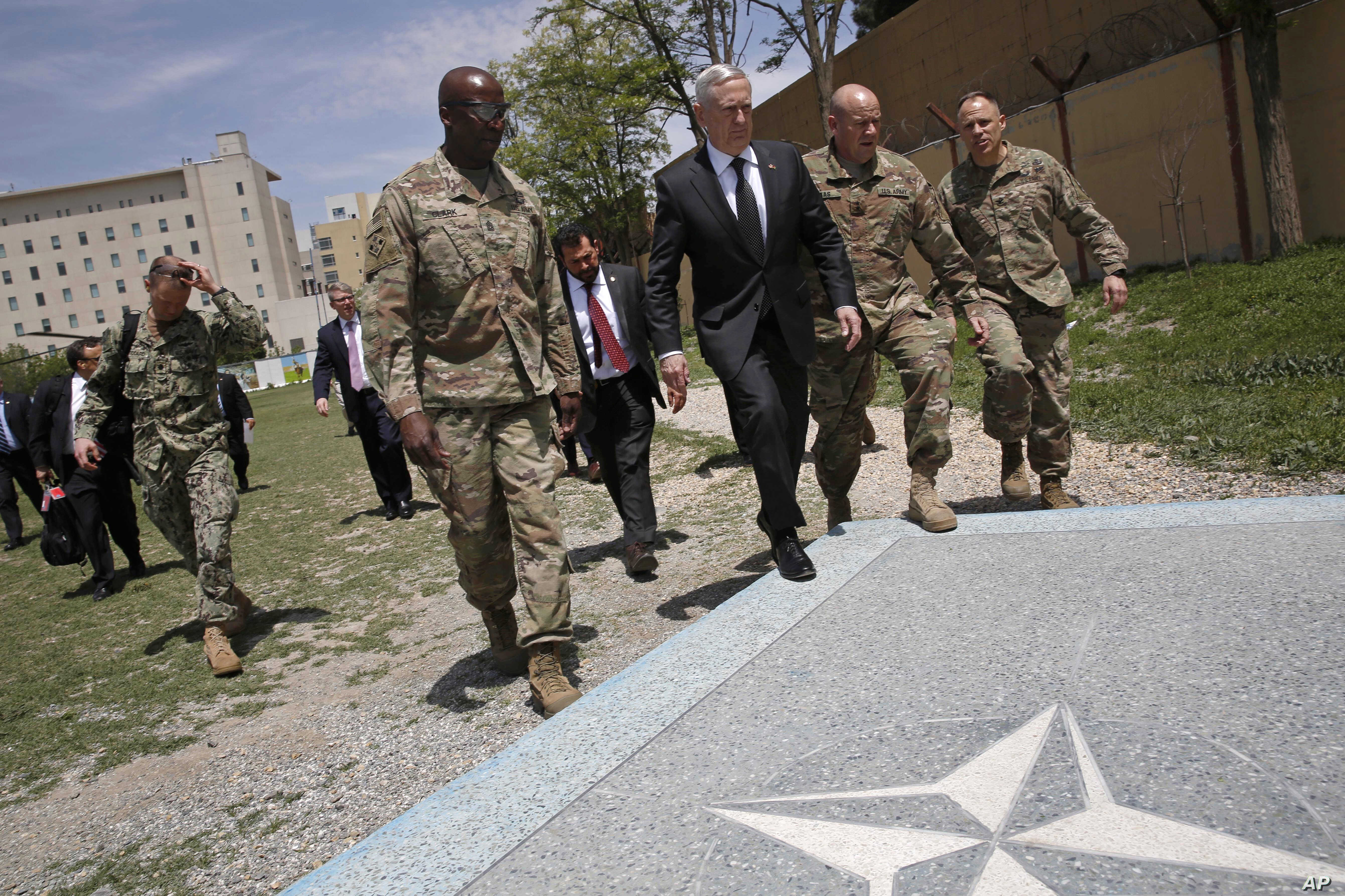 U.S. Defense Secretary James Mattis, third right, walks with U.S. Army Command Sergeant Major David Clark, left, and General Christopher Haas, second right, as he arrives at the Resolute Support headquarters in Kabul, Afghanistan,  April 24, 2017.