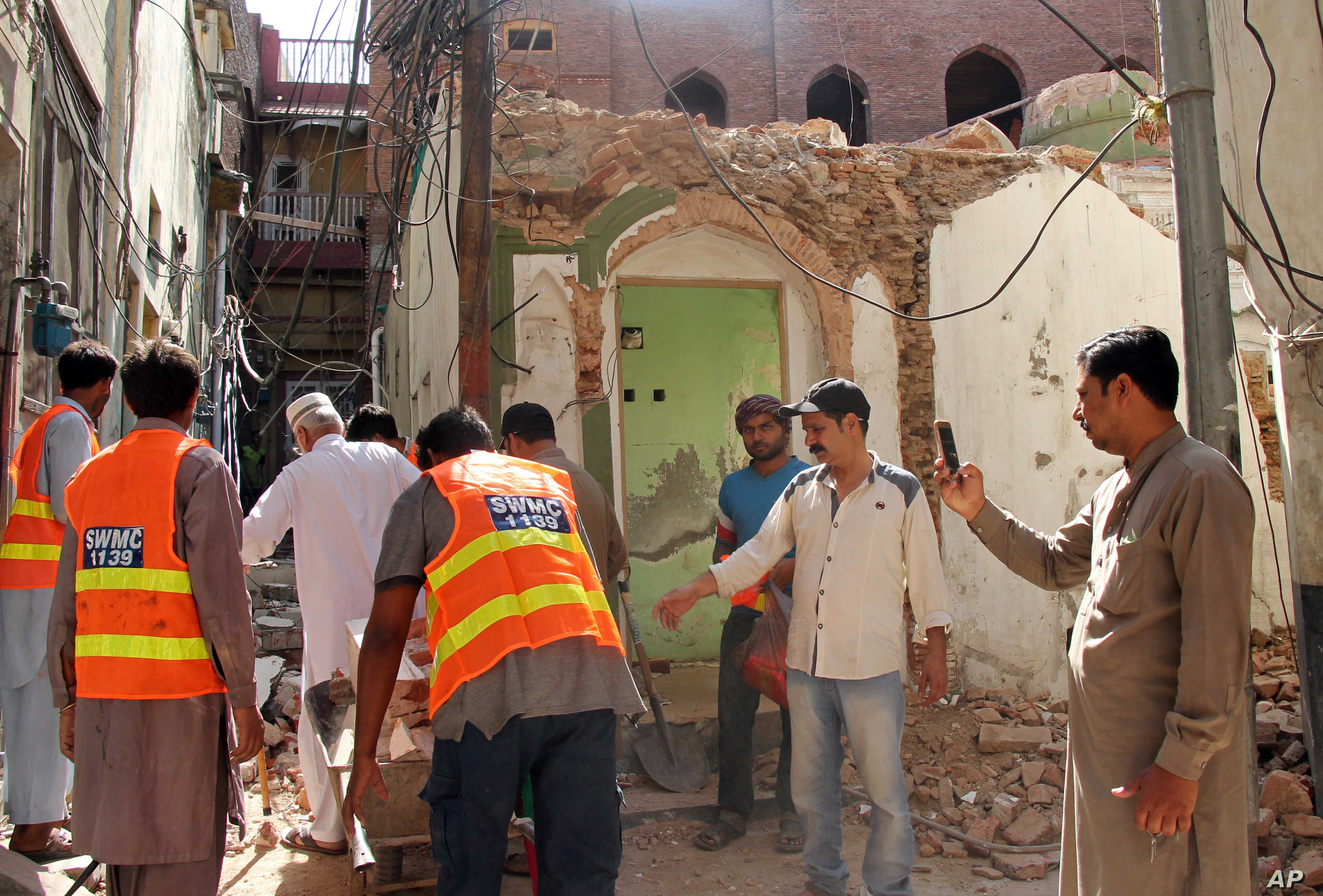 FILE - Pakistani volunteers collect debris from an Ahmadi mosque demolished by an angry mob, in the eastern city of Sialkot, May, 24, 2018.