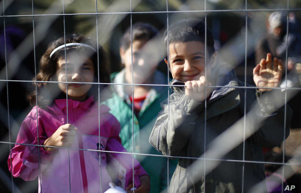 Children behind a fence in a temporary holding center for migrants near the border line between Serbia and Hungary in Roszke, southern Hungary in Roszke, Sept. 12, 2015.