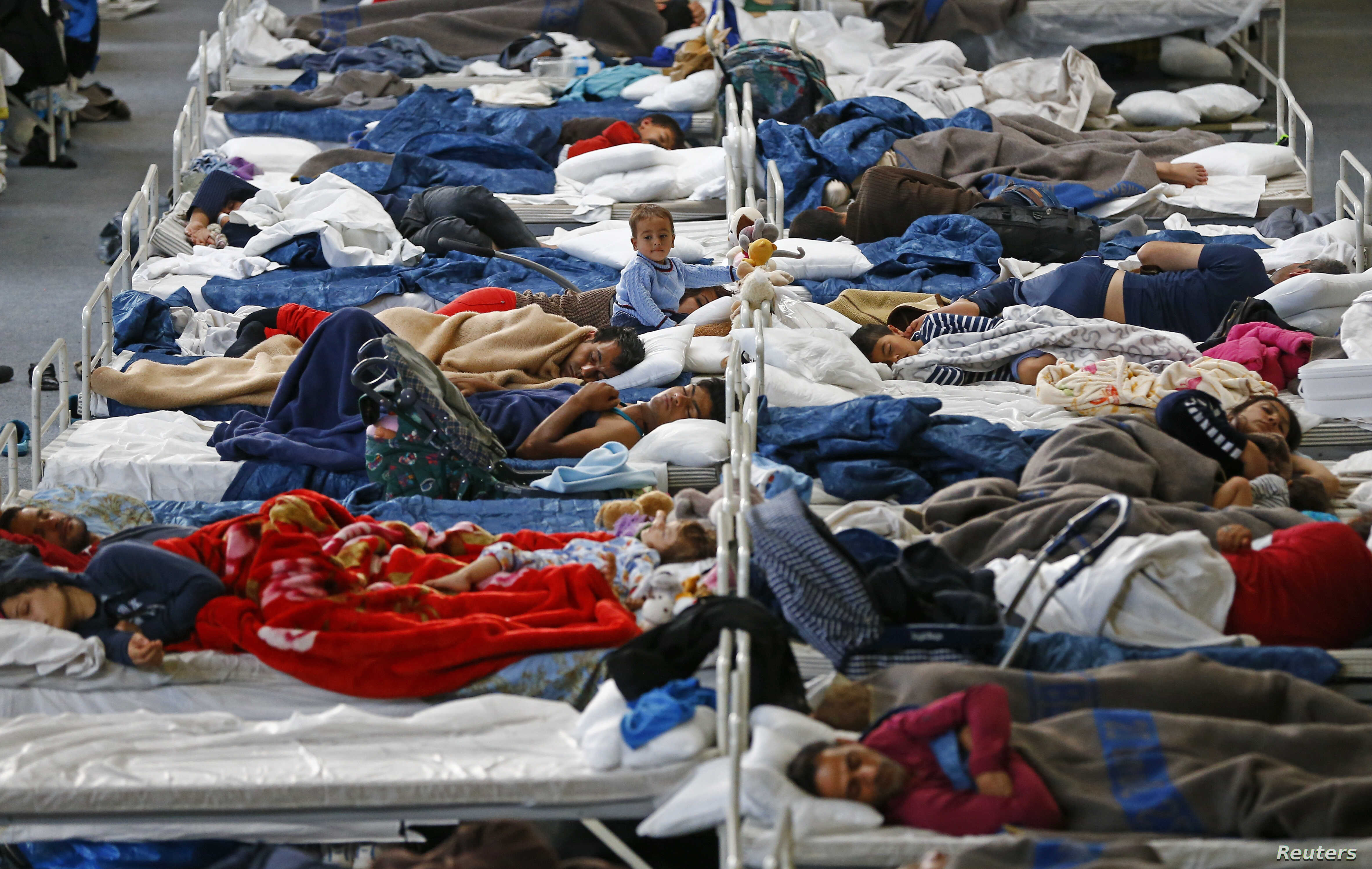 Migrants rest on beds at an improvised temporary shelter in a sports hall in Hanau, Germany, Sept. 22, 2015.