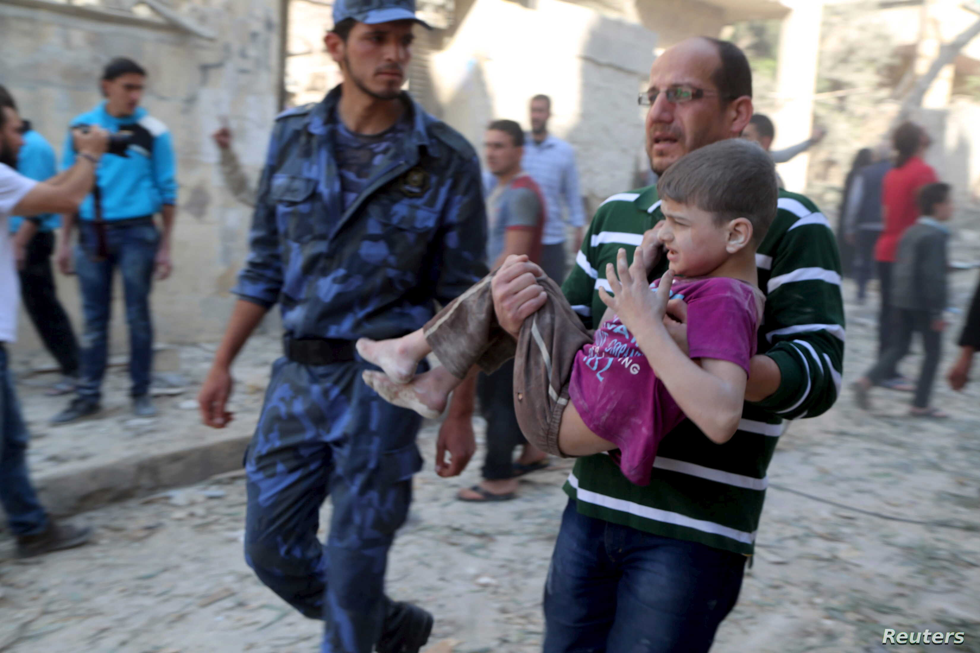 A man holds an injured boy after what activists said was a barrel bomb dropped by forces loyal to Syria's President Bashar al-Assad and hit a school and a residential building in Seif al-Dawla neighborhood of Aleppo, May 3, 2015.