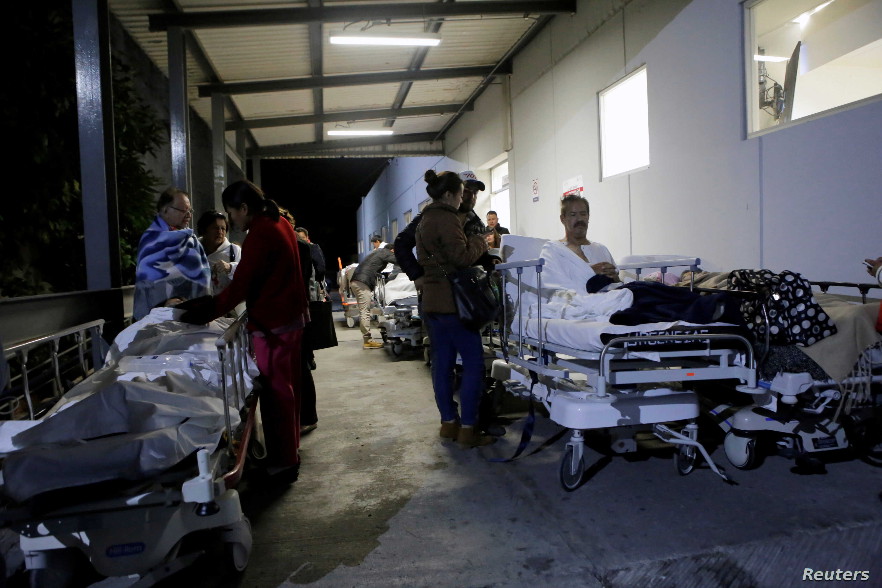 Patients and family members are seen outside the Institute for Social Security and Services for State Workers (ISSSTE) after an earthquake struck off the southern coast of Mexico late Thursday, in Puebla, Mexico, Sept. 8, 2017.