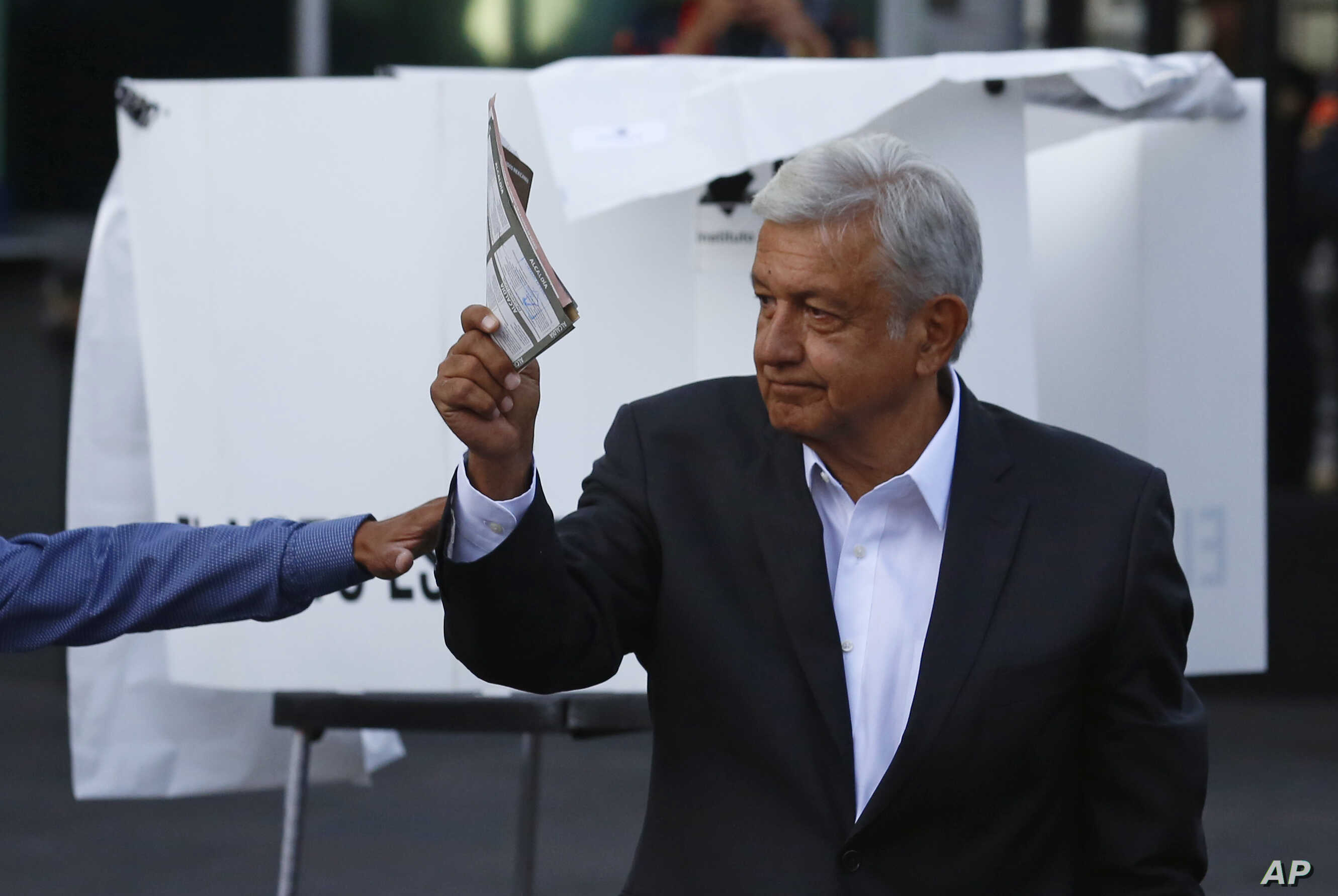 Presidential candidate Andres Manuel Lopez Obrador, of the MORENA party, shows his ballot to the press before casting it during general elections in Mexico City, July 1, 2018.
