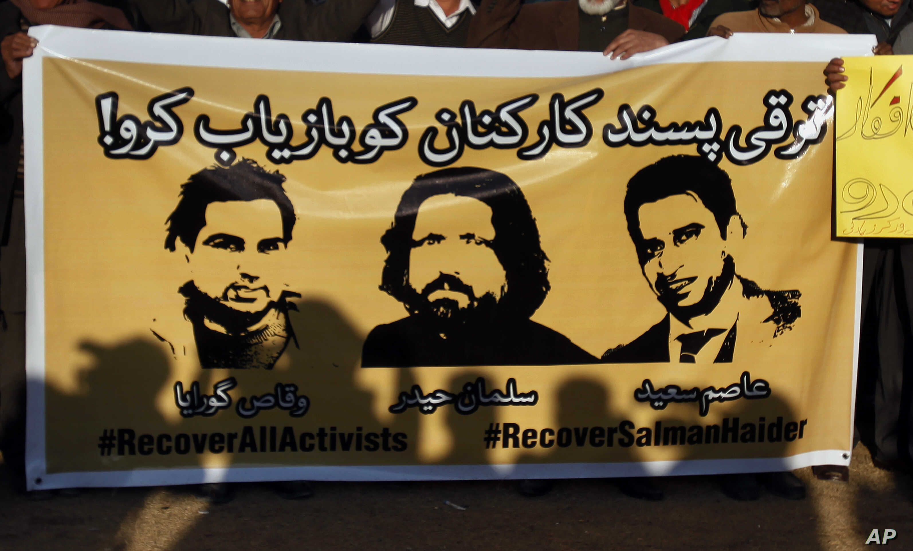 FILE - Members of civil society hold a banner with pictures of missing rights activists, Waqas Goraya, Salman Haider, and Asim Saeed, during a demonstration to condemn the missing human rights activists, in Islamabad, Pakistan, Jan. 10, 2017.